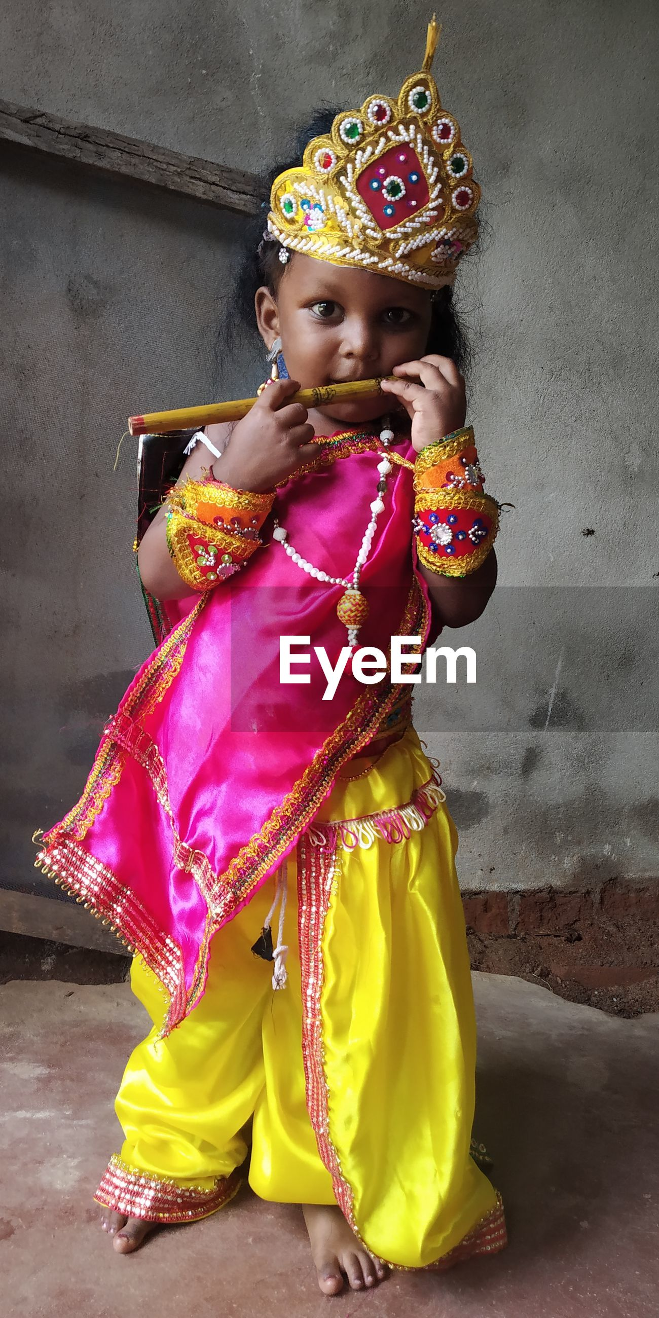 Full length of a baby krishna looking away