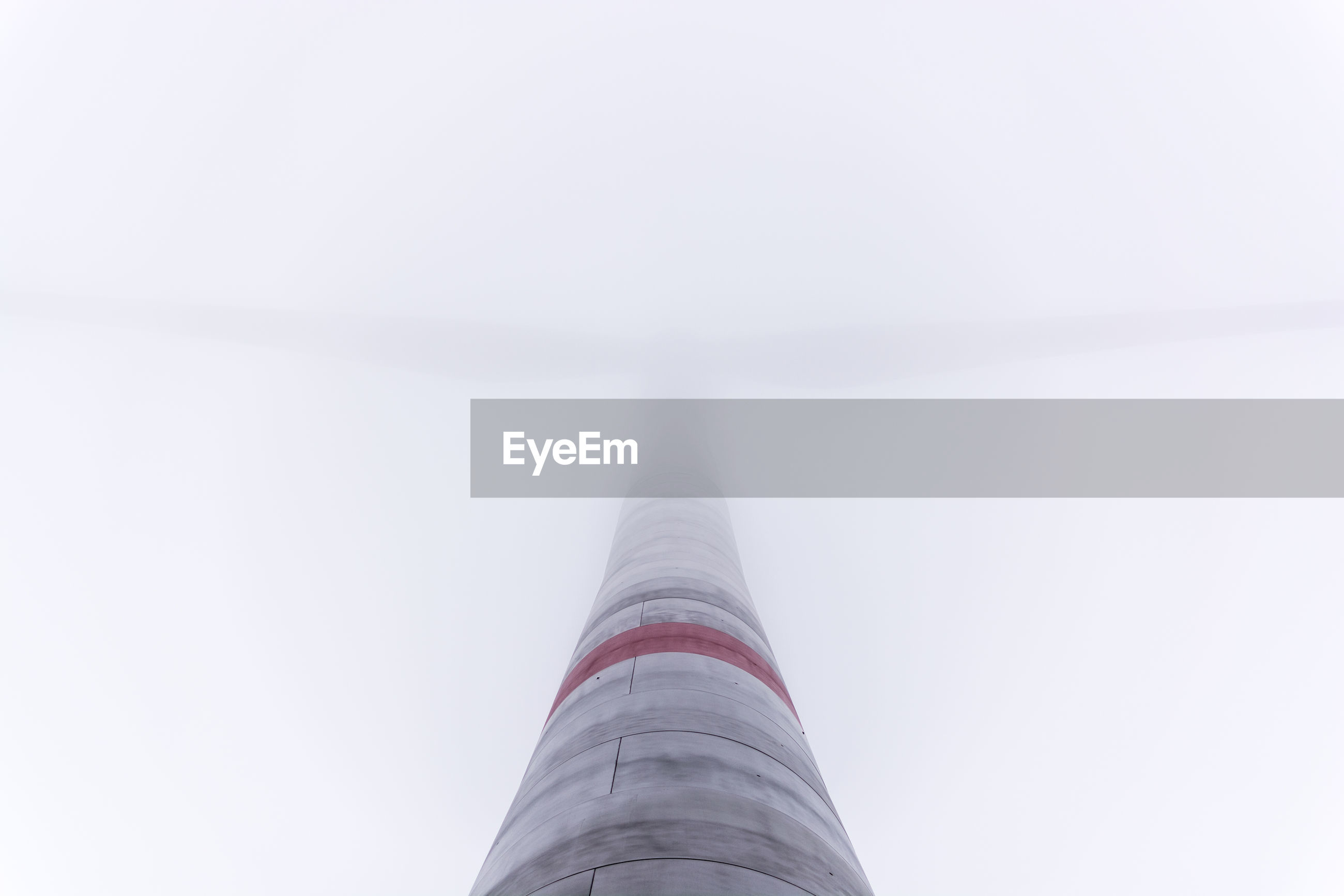 Low angle view of wind turbine in foggy weather