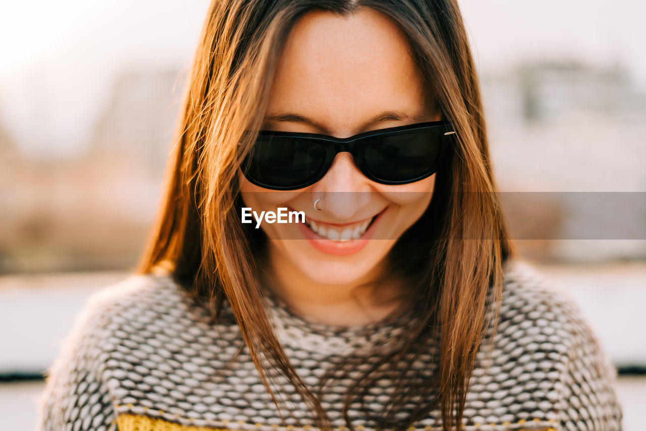 Close-up of smiling woman wearing sunglasses looking down