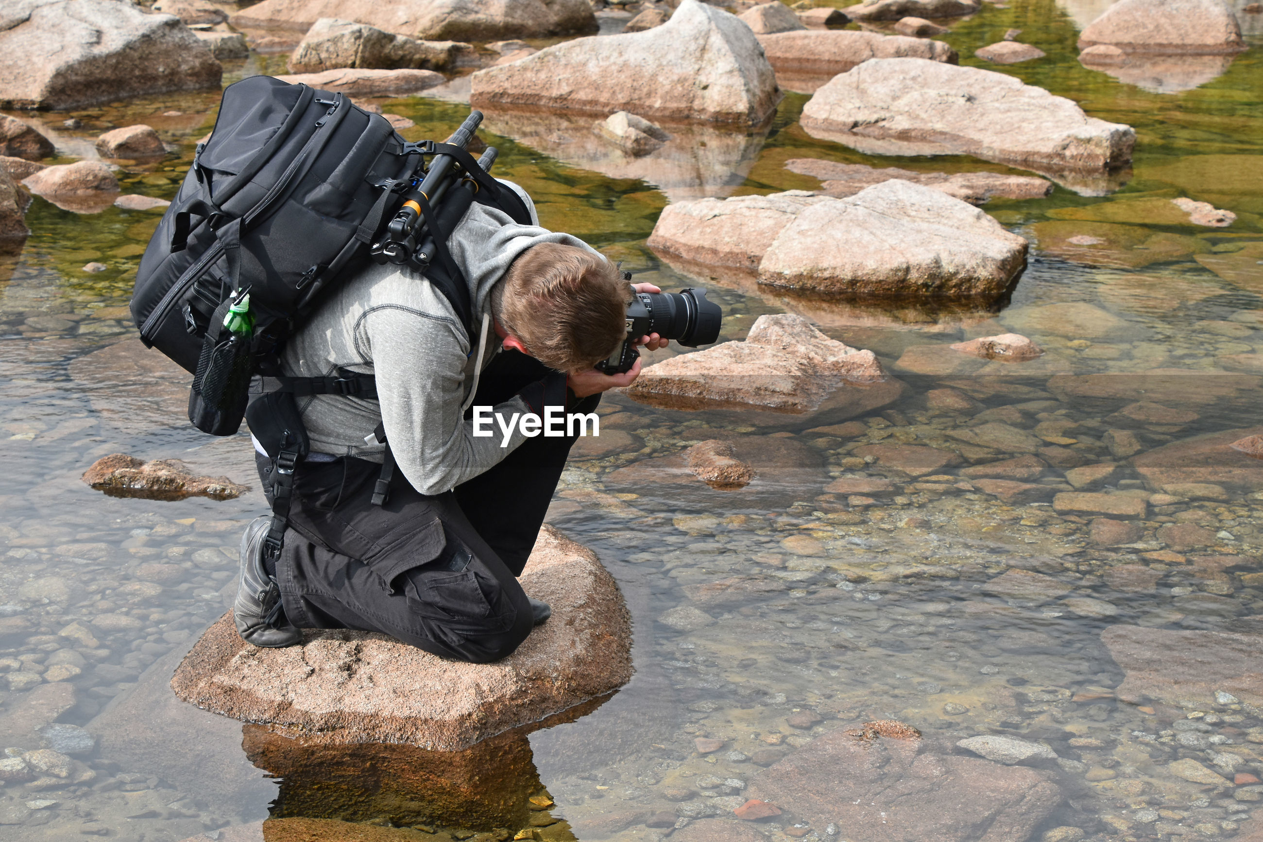 Man photographing on rock in skalnate pleso lake