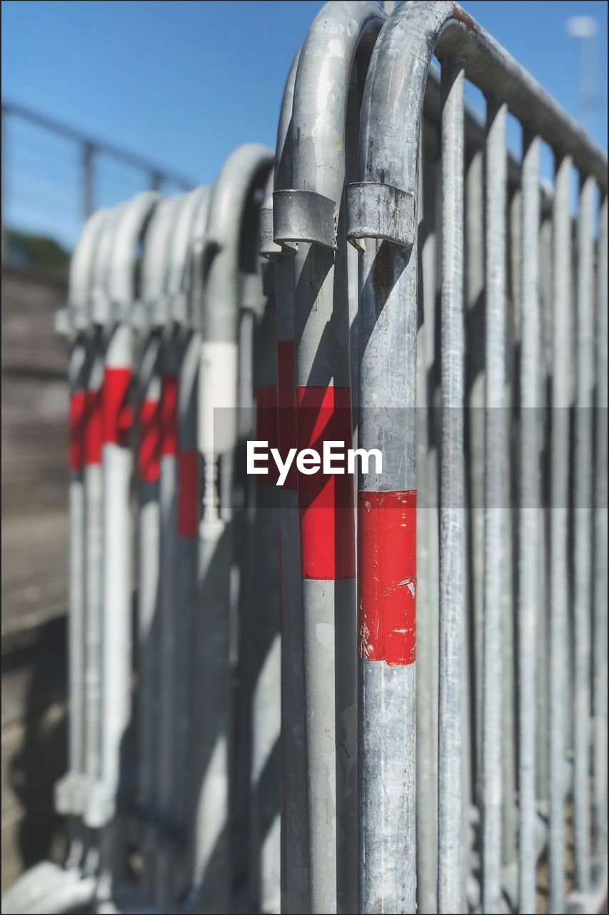 red, safety, metal, security, selective focus, protection, no people, barrier, close-up, boundary, day, fence, railing, hanging, focus on foreground, in a row, outdoors, sunlight, nature, architecture, silver colored
