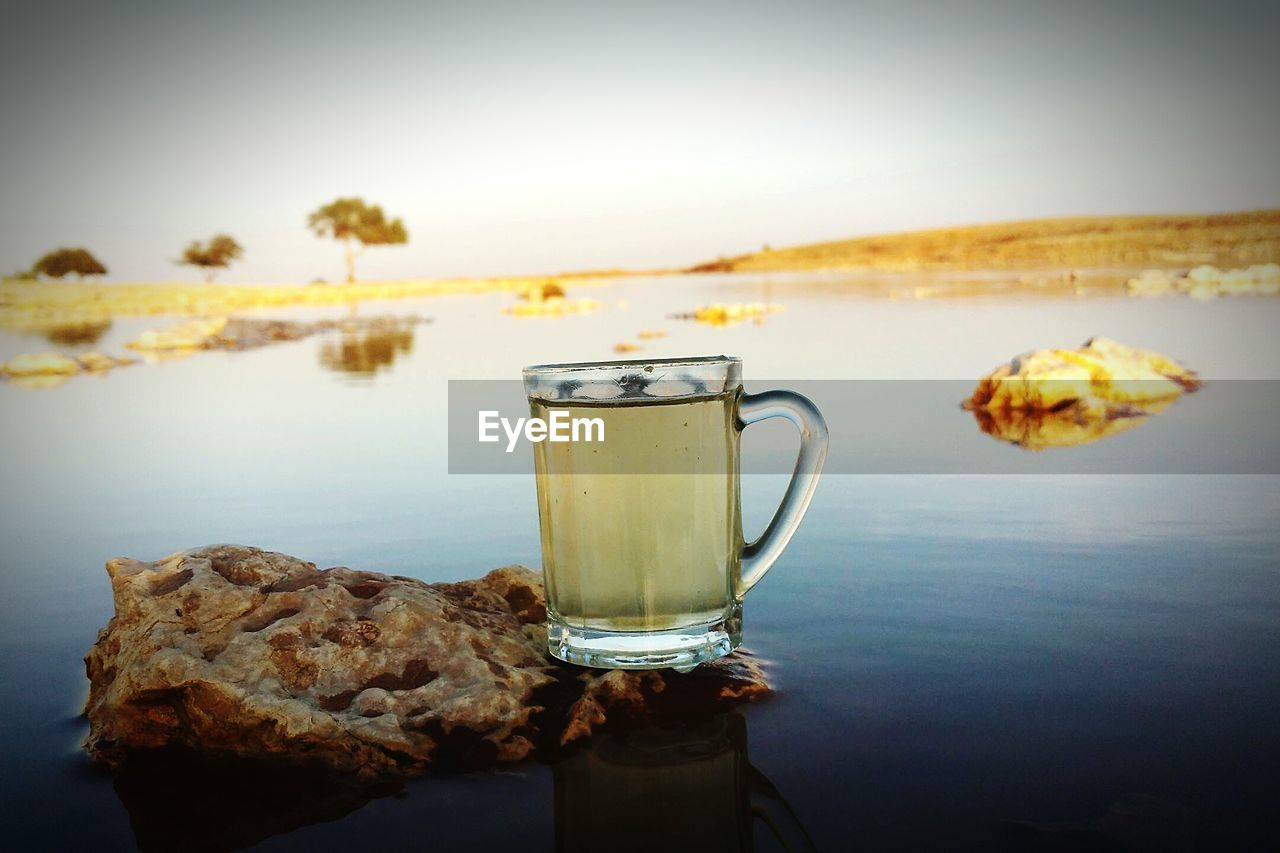 Drink in glass on rock against lake
