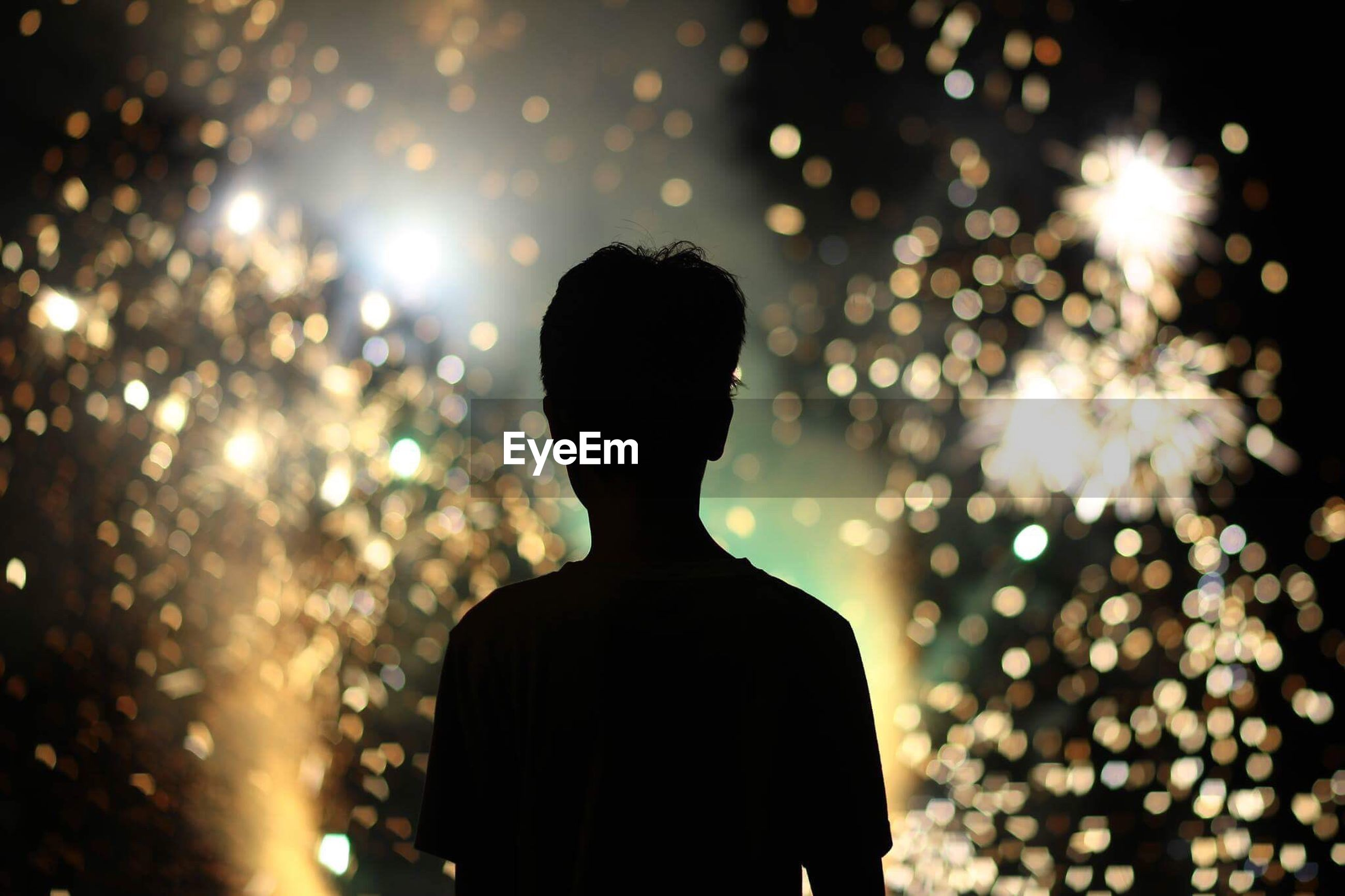 Rear view of silhouette man against illuminated sparklers at night