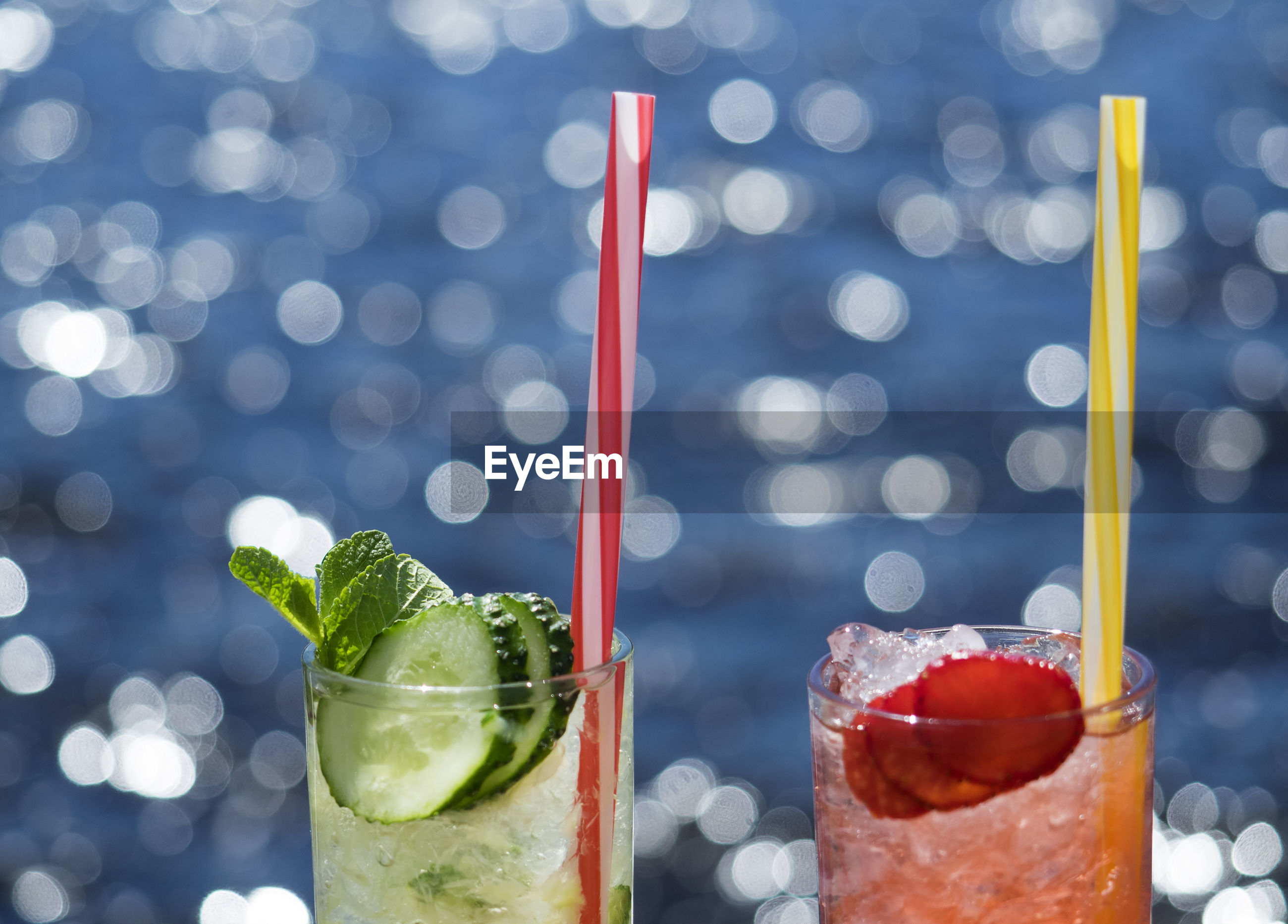 Close-up of lemonades in glasses against sea