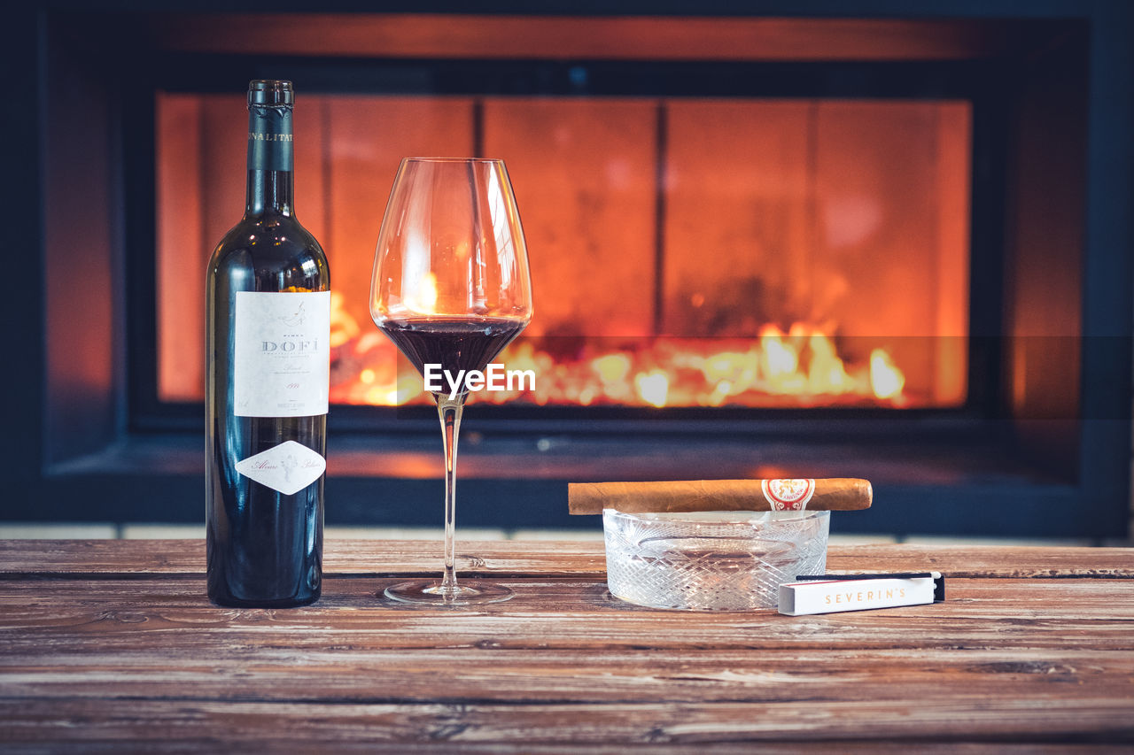 table, drink, food and drink, glass, refreshment, glass - material, indoors, container, burning, flame, wineglass, fire, focus on foreground, wood - material, bottle, no people, fire - natural phenomenon, wine, alcohol, still life, red wine, tray