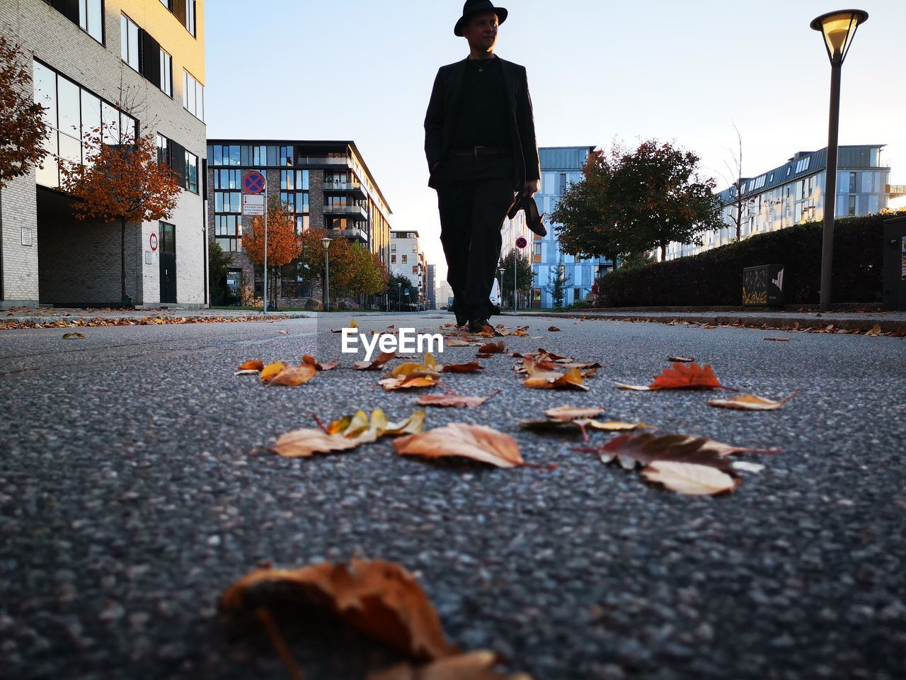 Man walking on leaves in city