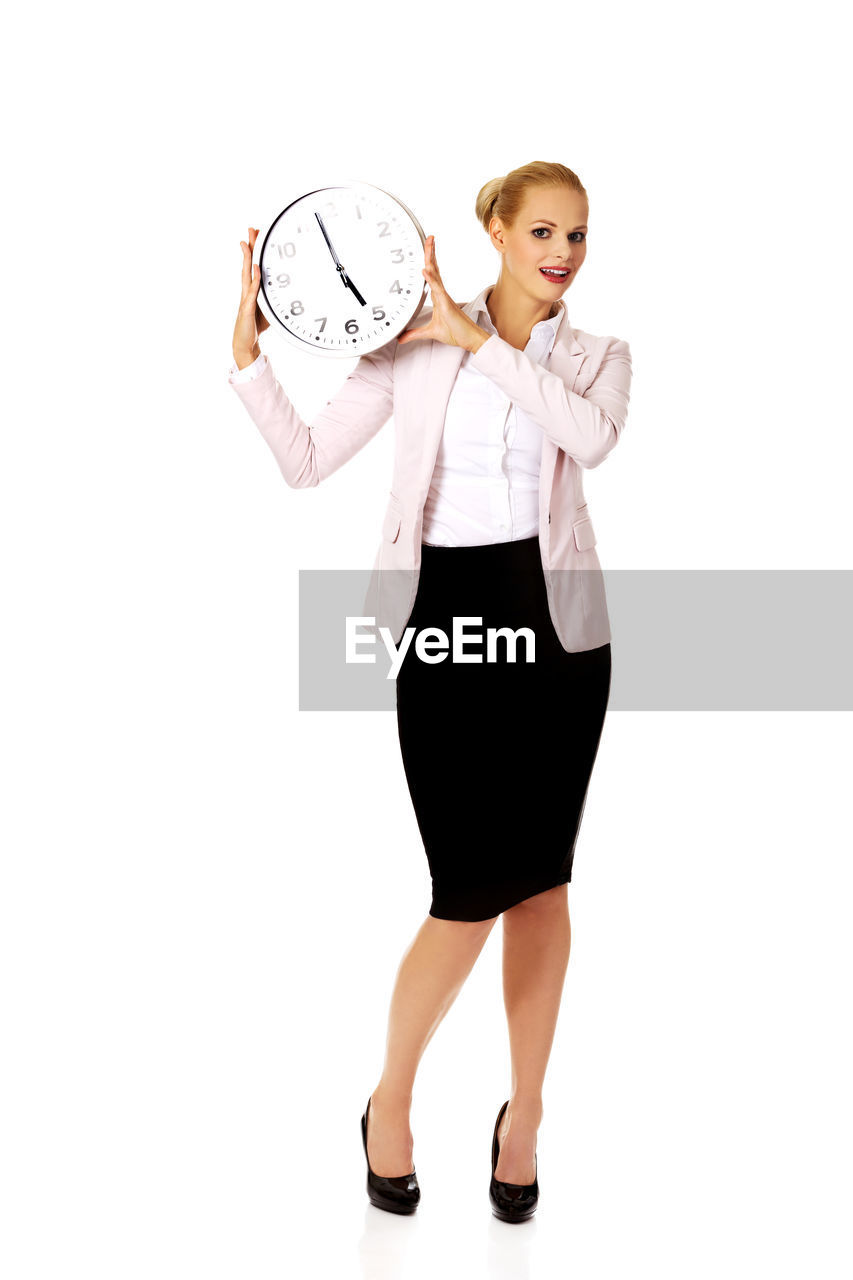 Portrait Of Businesswoman Holding Clock Against White Background