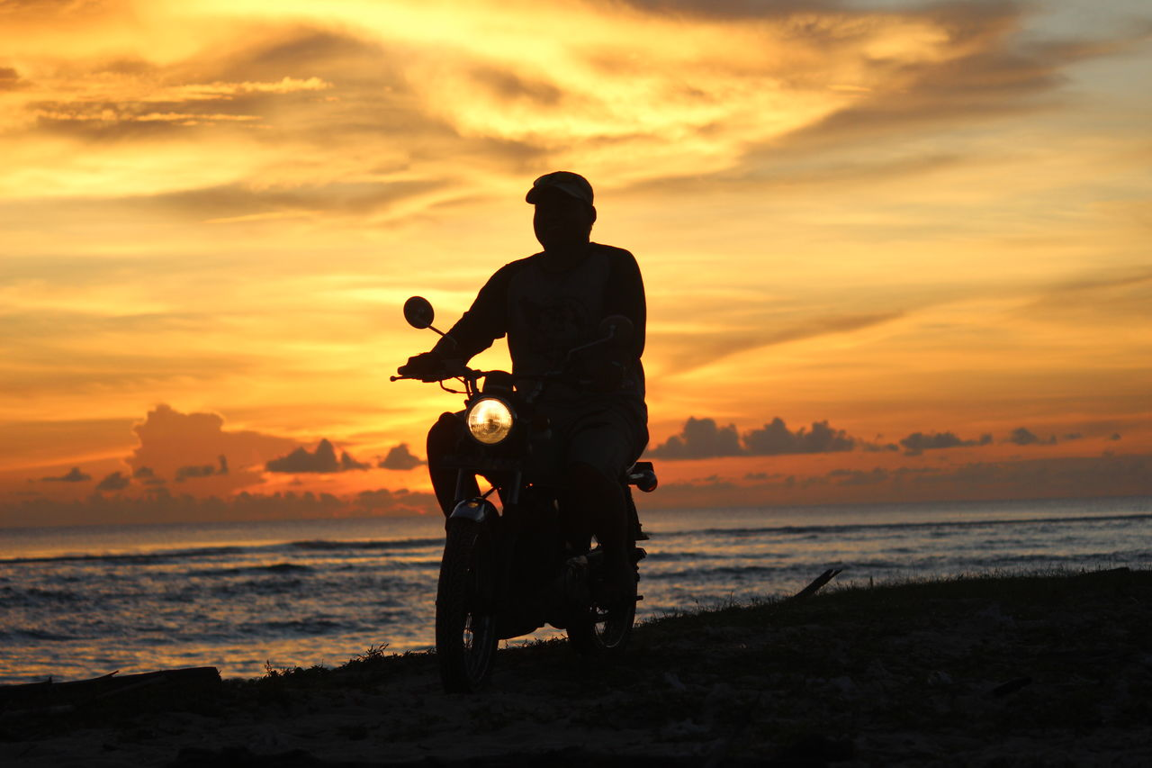 Silhouette man riding motorcycle at beach against sky during sunset