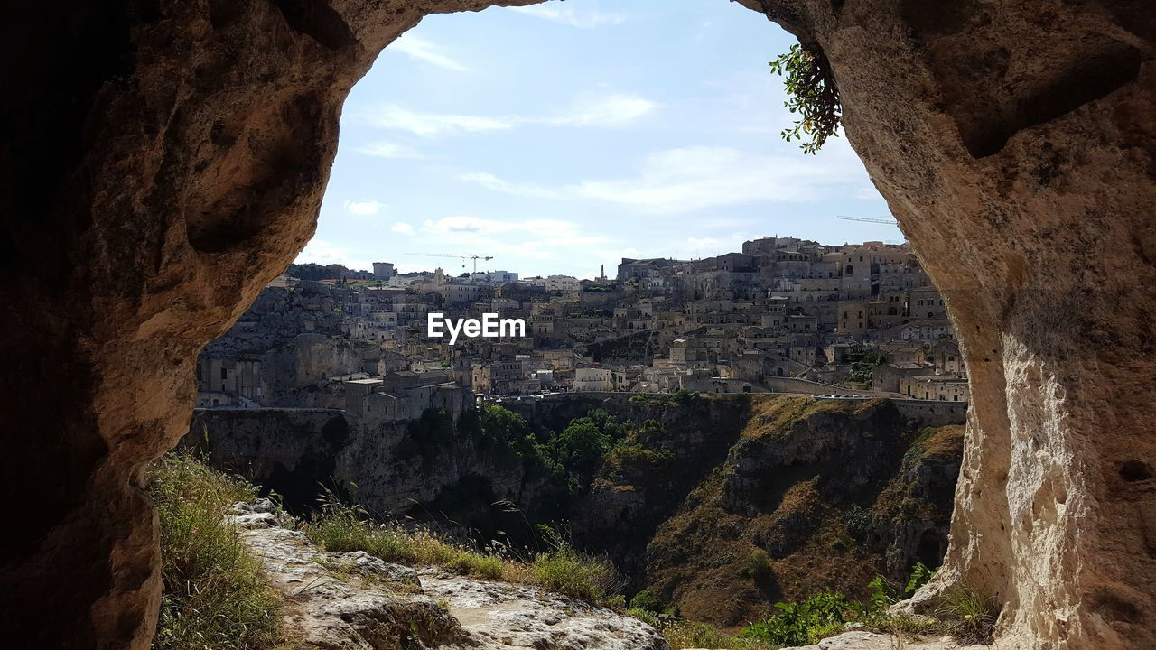 Buildings seen through hole in rock formation against sky