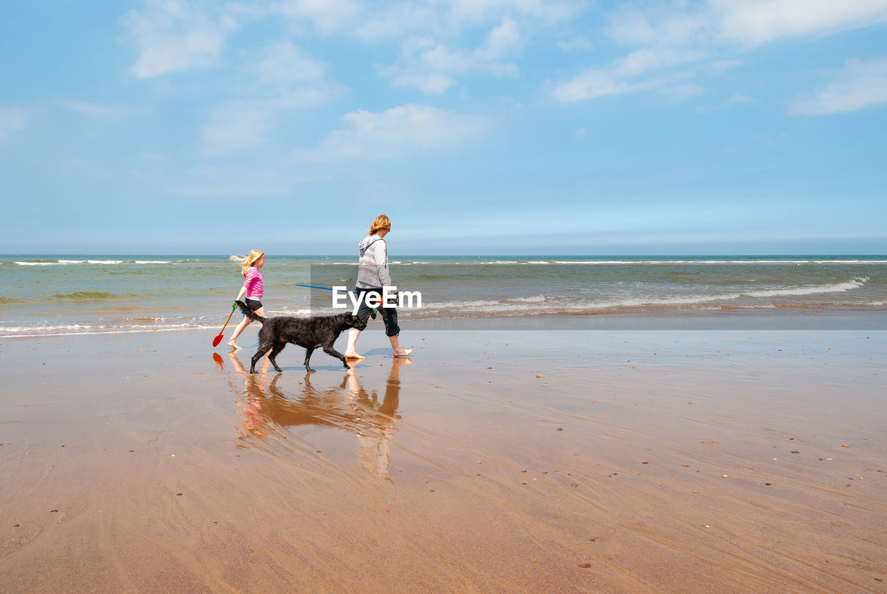 PEOPLE WITH DOG ON BEACH