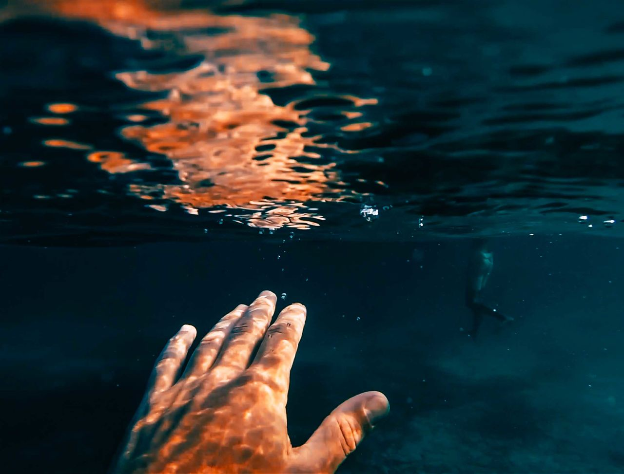 Cropped Image Of Person Hand Underwater