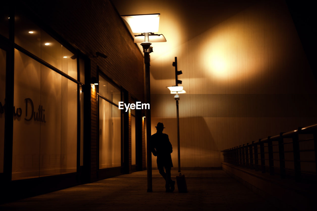 illuminated, one person, real people, full length, lighting equipment, lifestyles, architecture, men, night, indoors, young adult