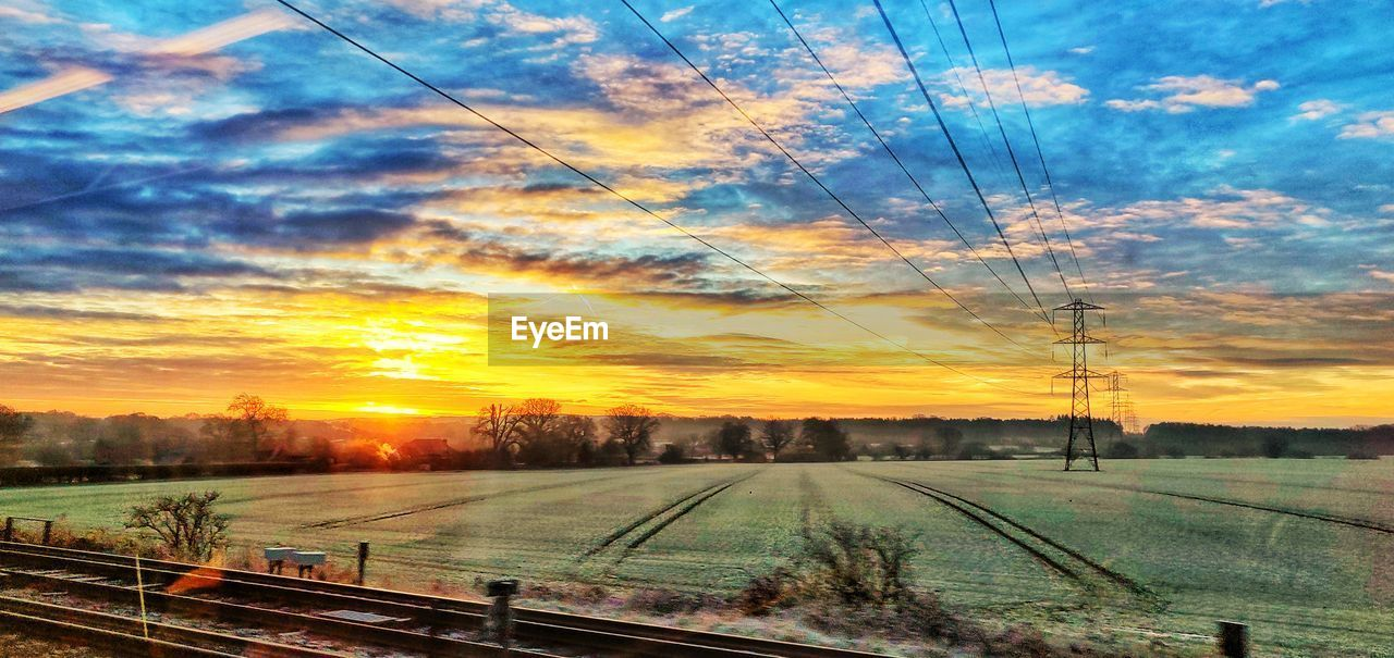 sky, sunset, cloud - sky, rail transportation, track, nature, railroad track, cable, electricity, beauty in nature, orange color, no people, transportation, power line, electricity pylon, train, technology, scenics - nature, plant, outdoors, power supply