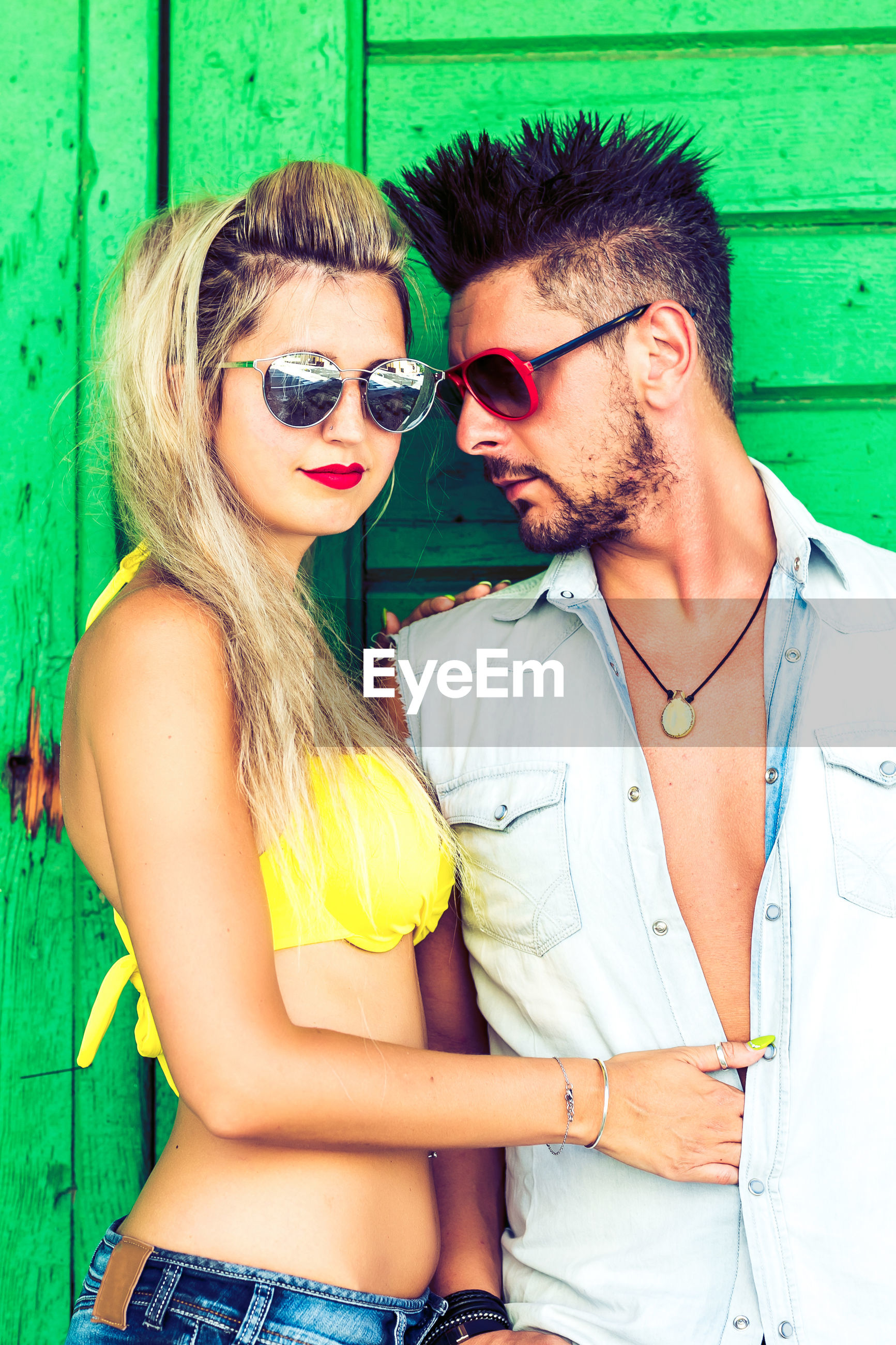 Couple wearing sunglasses against green wall