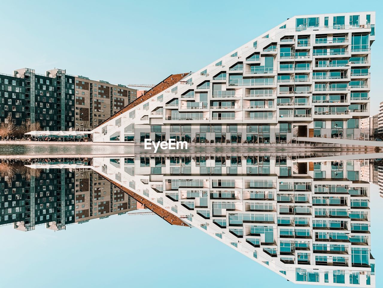 building exterior, built structure, architecture, building, sky, water, waterfront, reflection, clear sky, city, no people, day, nature, symmetry, residential district, office building exterior, lake, blue, outdoors, skyscraper