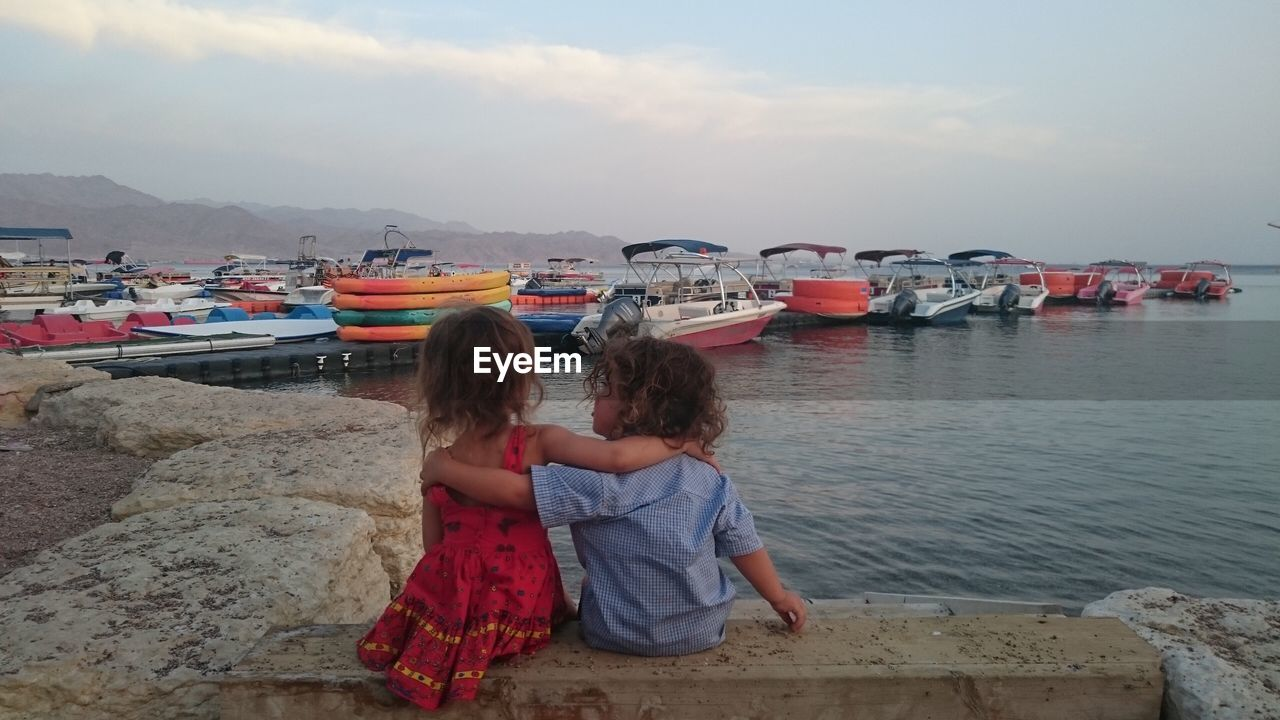 Rear view of siblings with arms around on retaining wall against boats