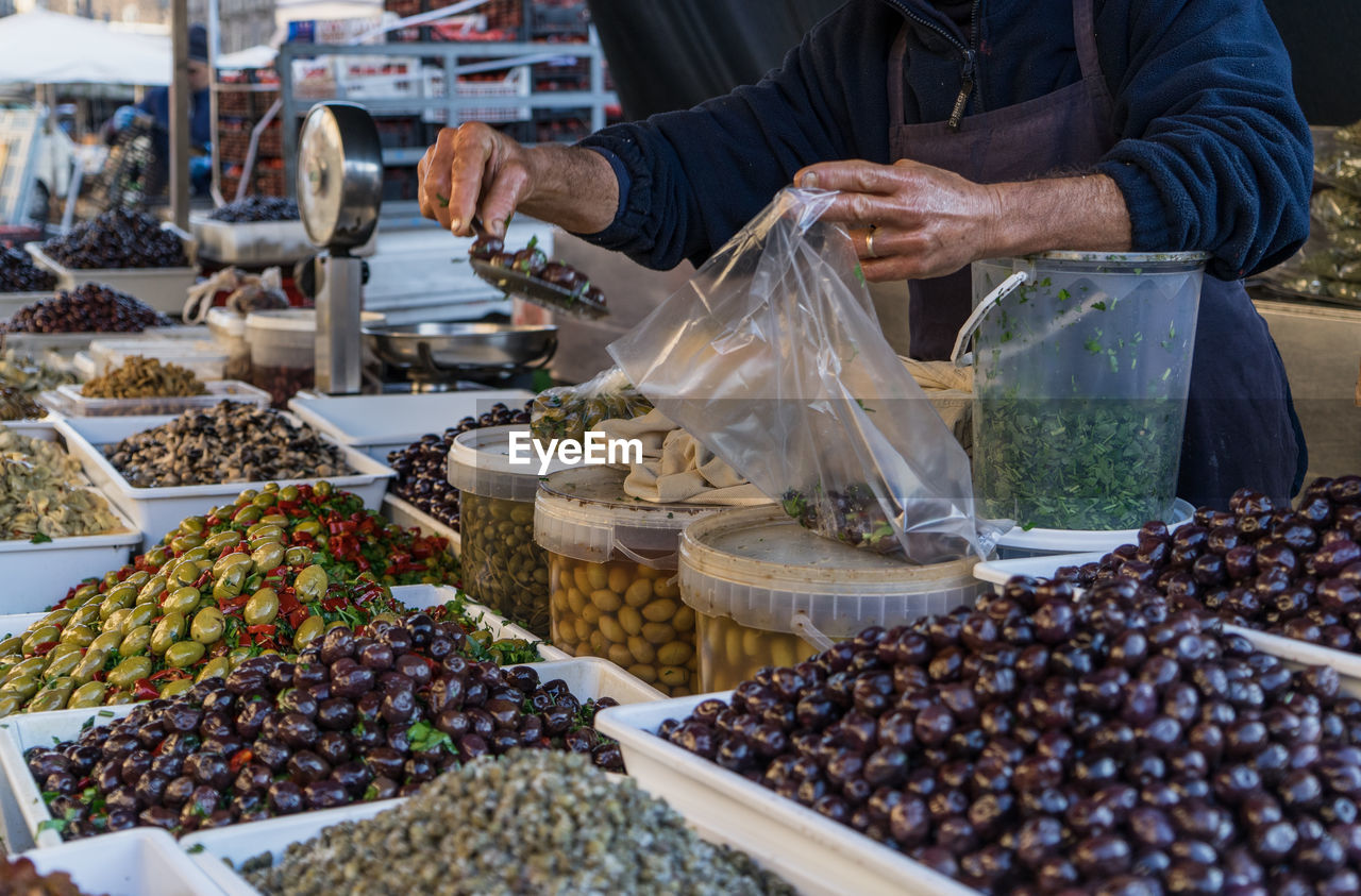 Midsection Of Vendor Packing Olives In Bag At Market Stall