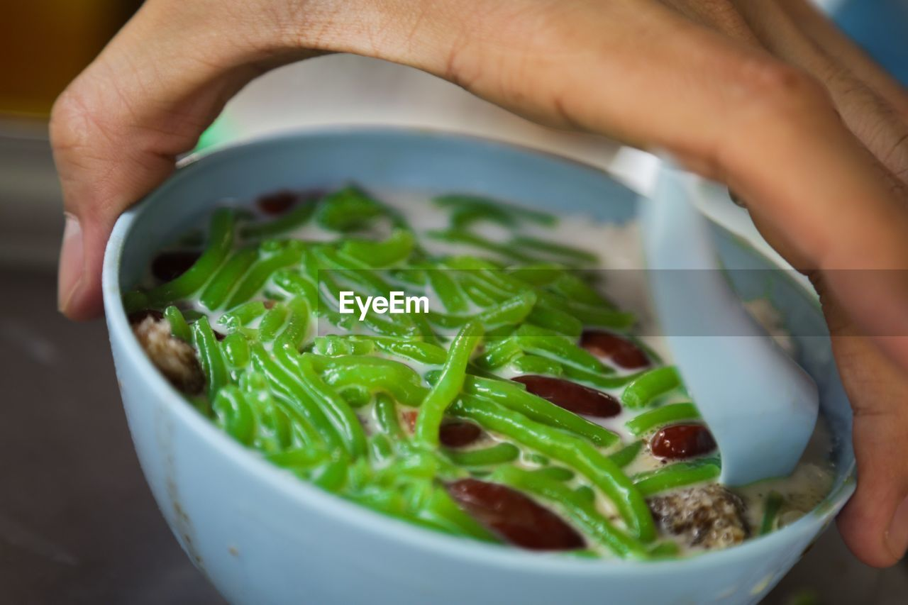 Close-Up Of Hand Holding Cendol In Bowl