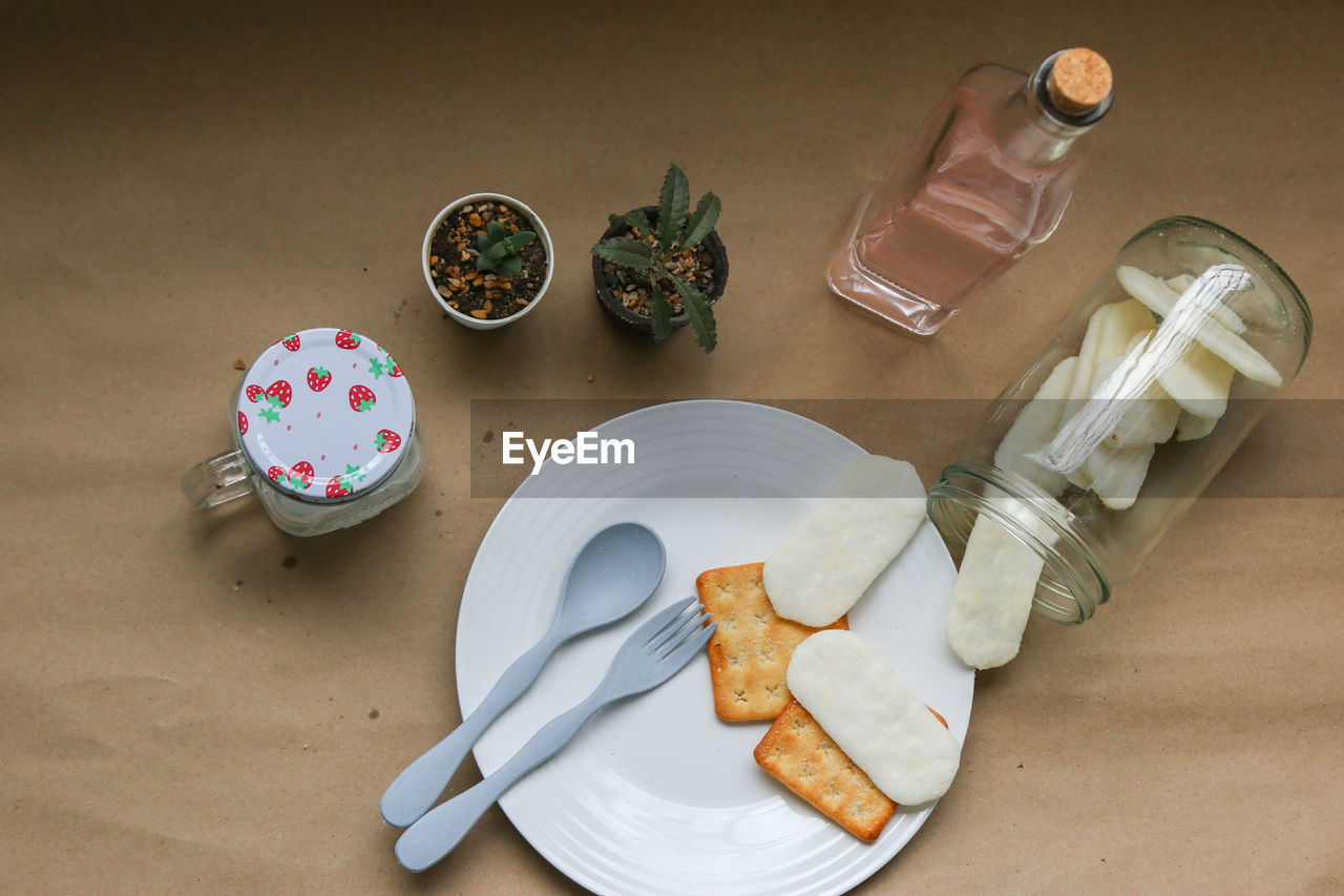 food and drink, table, still life, high angle view, food, indoors, container, bottle, freshness, no people, eating utensil, plate, kitchen utensil, drink, close-up, refreshment, glass, spoon, household equipment