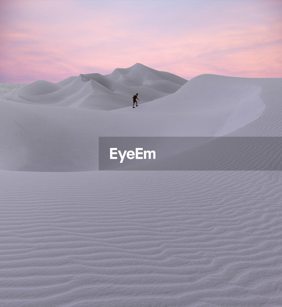 Man walking on desert against sky during sunset