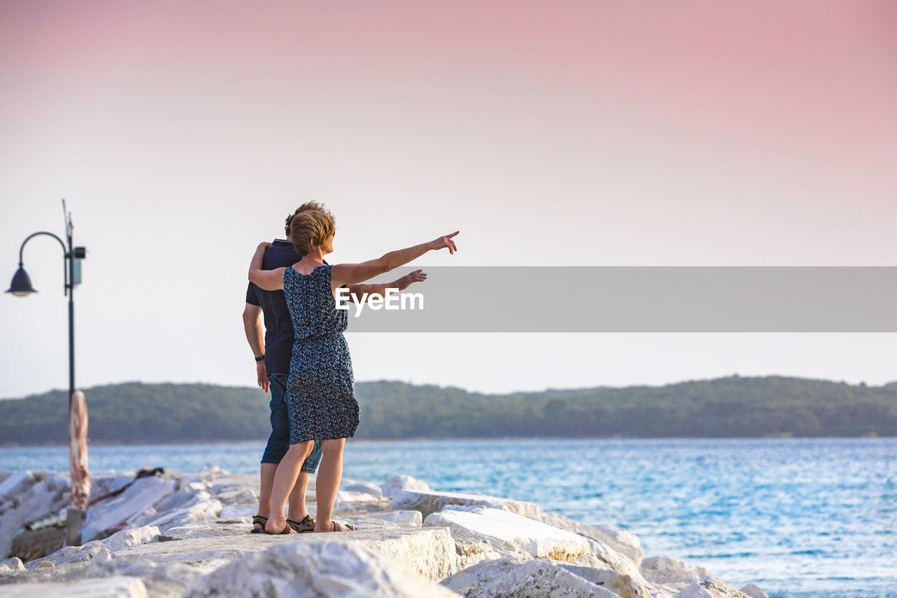 Full length of couple standing on pier by sea against clear sky