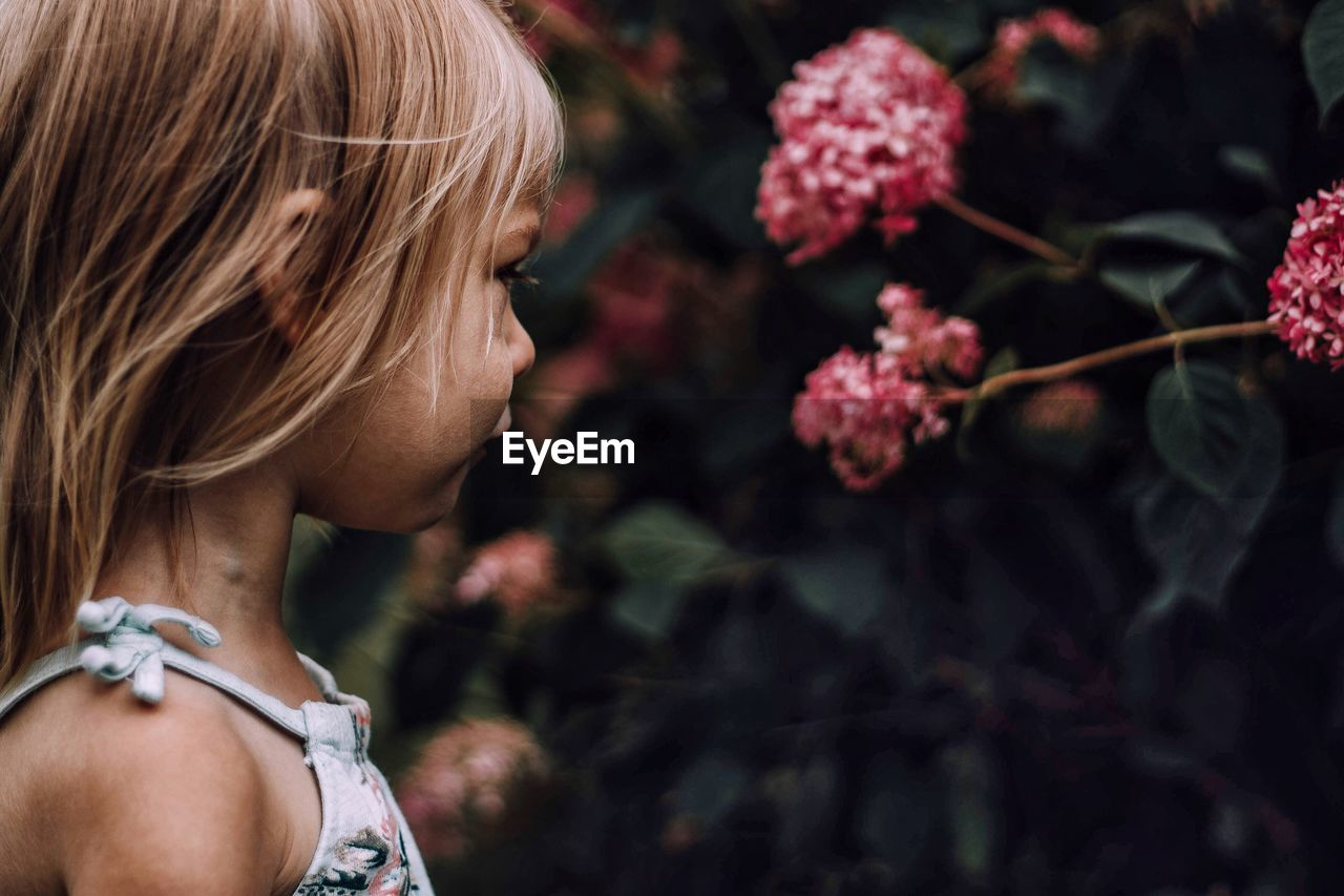 Close-up of girl looking at flowers blooming outdoors