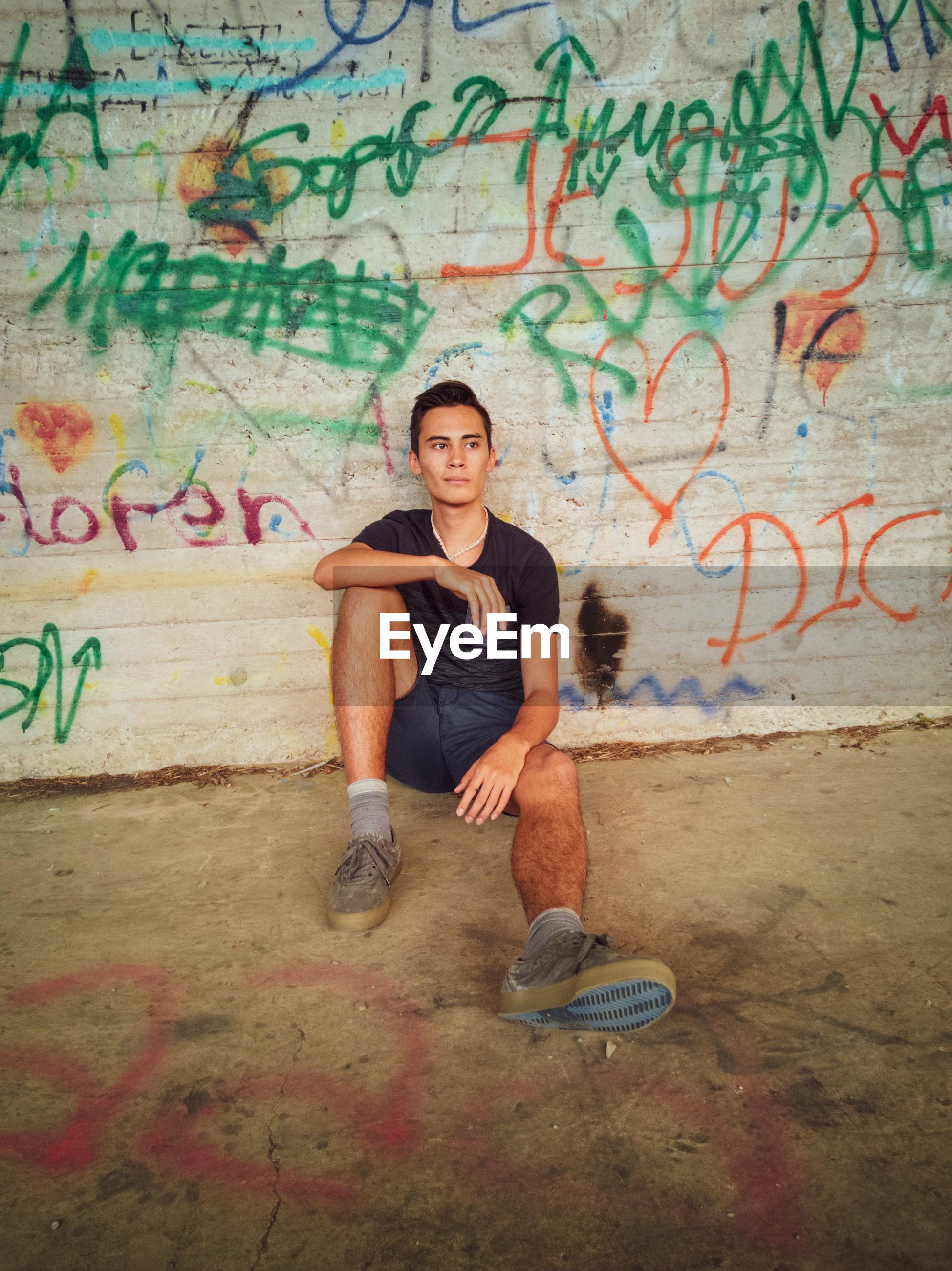 Full length of man sitting against graffiti wall