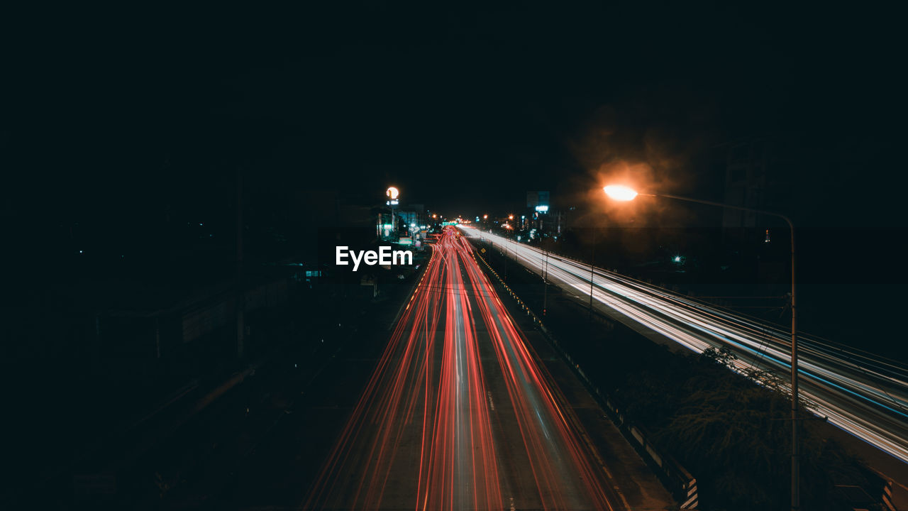 illuminated, night, architecture, city, light trail, lighting equipment, long exposure, motion, transportation, street, speed, no people, road, built structure, direction, the way forward, tail light, street light, high angle view, highway, outdoors, light, multiple lane highway, vehicle light