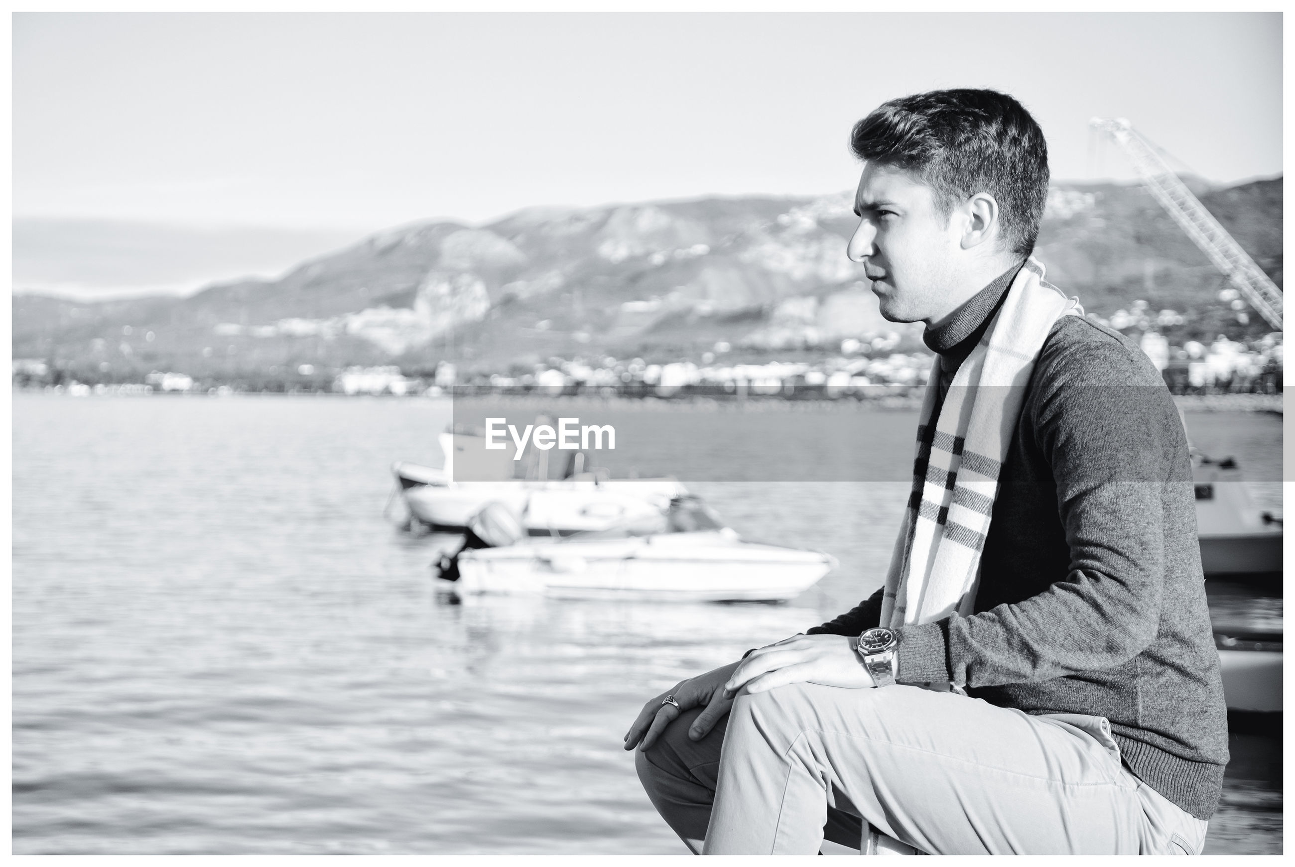 Side view of young man sitting by lake against sky
