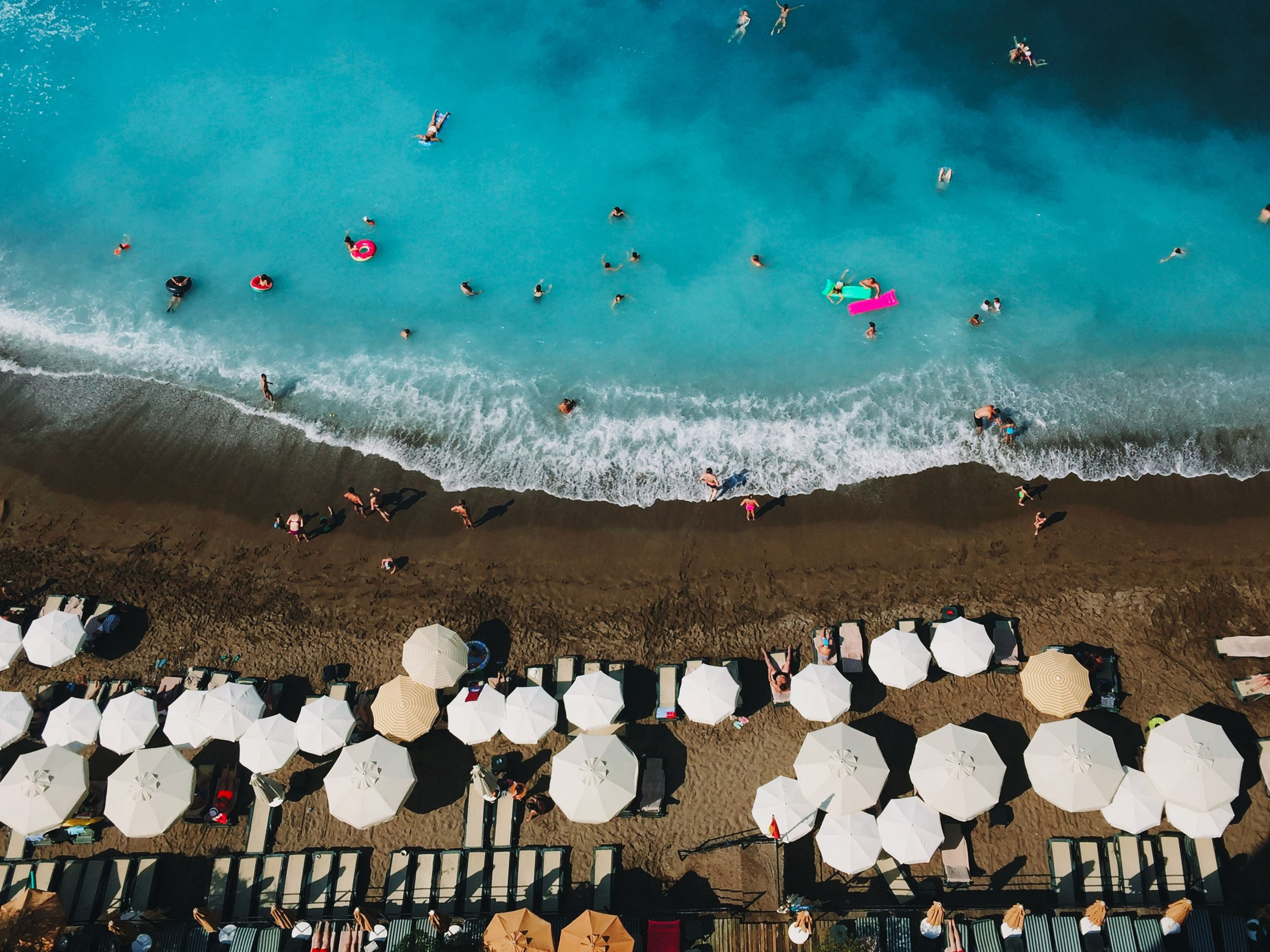 High angle view of people and umbrellas at beach on sunny day