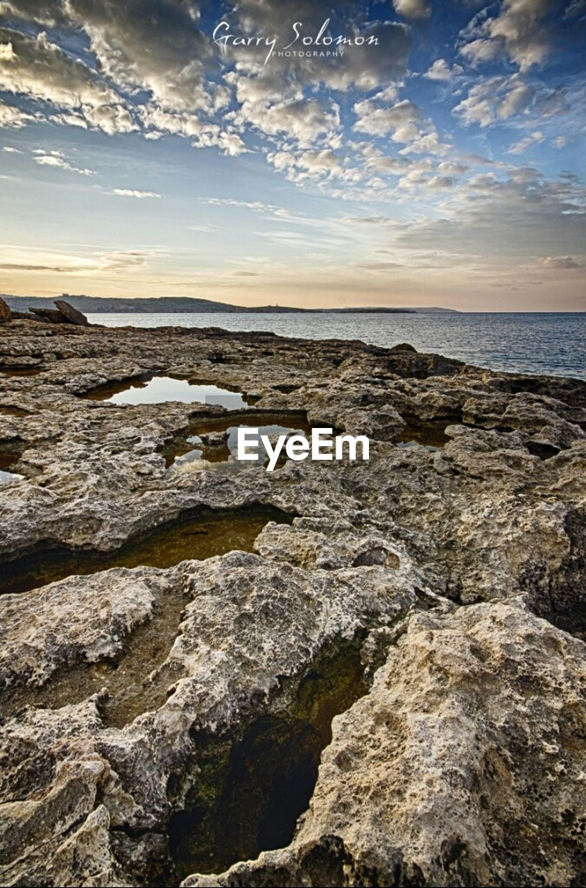 cloud - sky, sky, sunset, scenics, landscape, nature, outdoors, rock - object, travel destinations, tranquility, sunlight, beauty in nature, no people, water, horizon, sea, horizon over water, beach, day