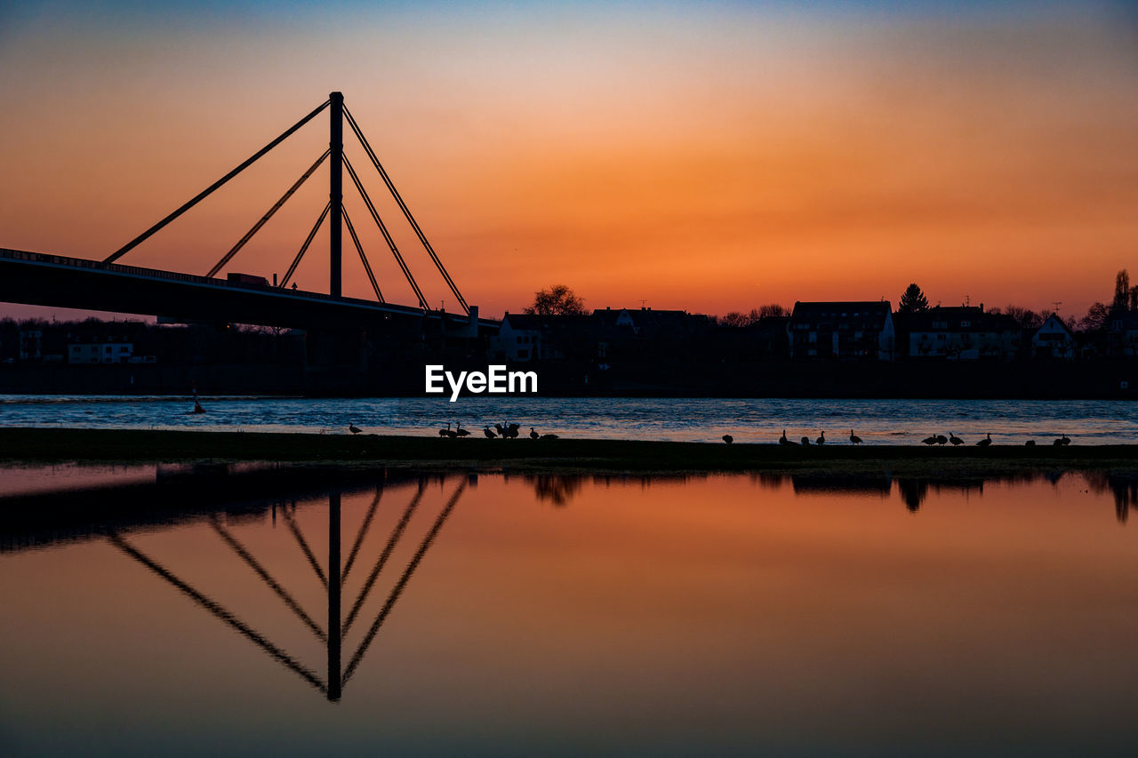 sunset, reflection, water, built structure, sky, architecture, bridge - man made structure, orange color, connection, river, outdoors, waterfront, nature, building exterior, no people, scenics, travel destinations, city, beauty in nature, day