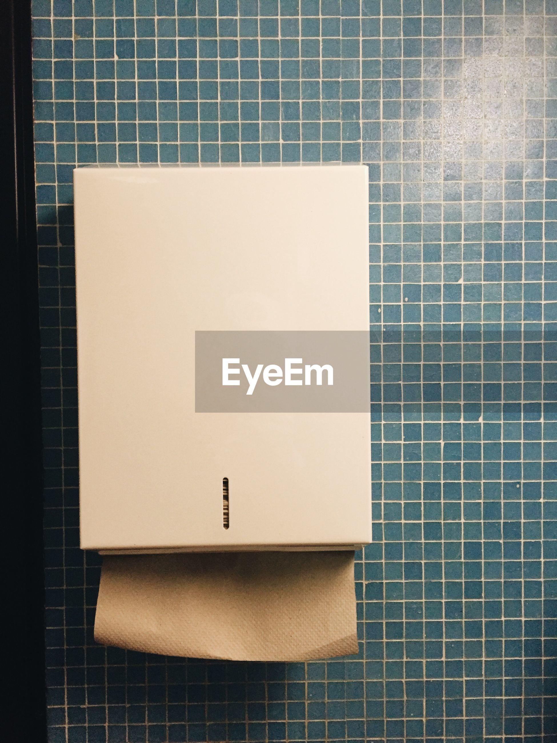 Towel dispenser on tiled wall in bathroom