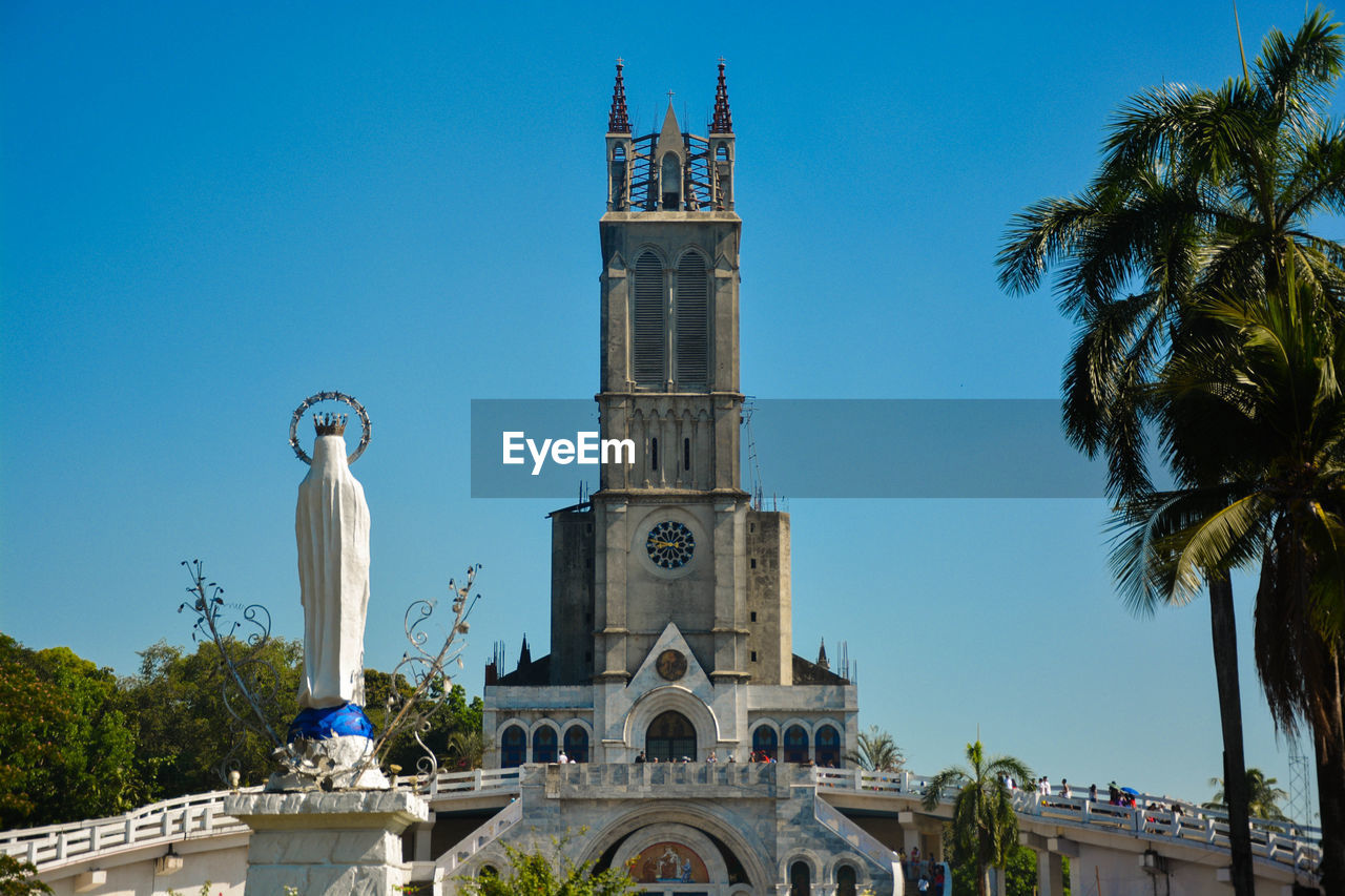 sky, built structure, architecture, tree, building exterior, plant, religion, belief, nature, palm tree, tower, spirituality, place of worship, clear sky, travel destinations, building, blue, tropical climate, no people, outdoors, spire