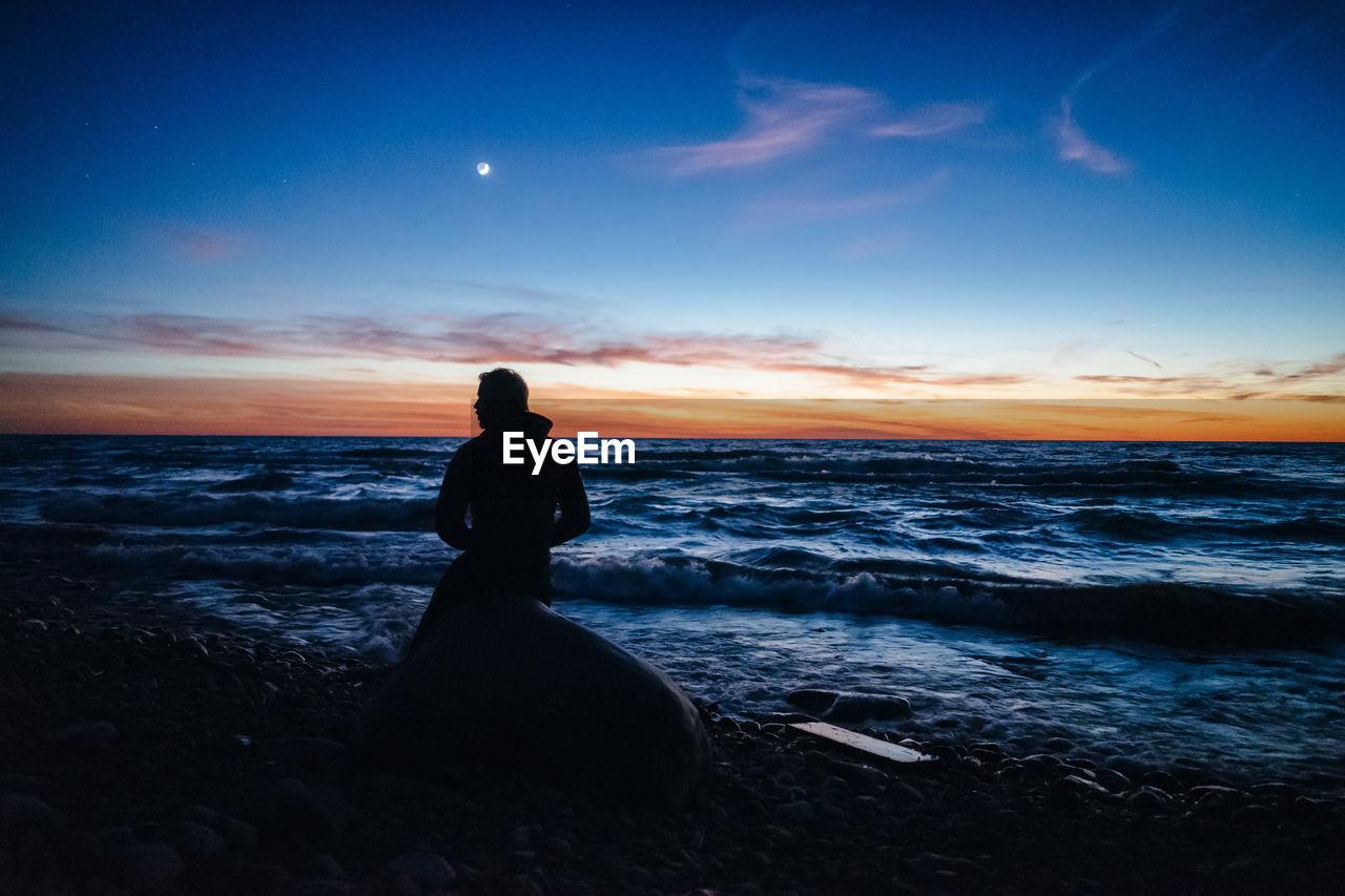 MAN SITTING ON BEACH DURING SUNSET