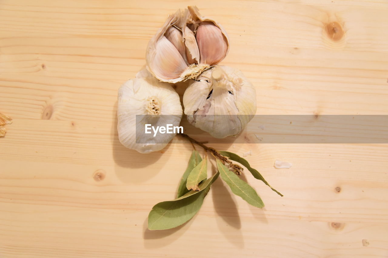 wood - material, food and drink, spice, table, freshness, food, garlic, ingredient, still life, no people, indoors, close-up, garlic bulb, wellbeing, healthy eating, vegetable, high angle view, directly above, raw food, plant, garlic clove