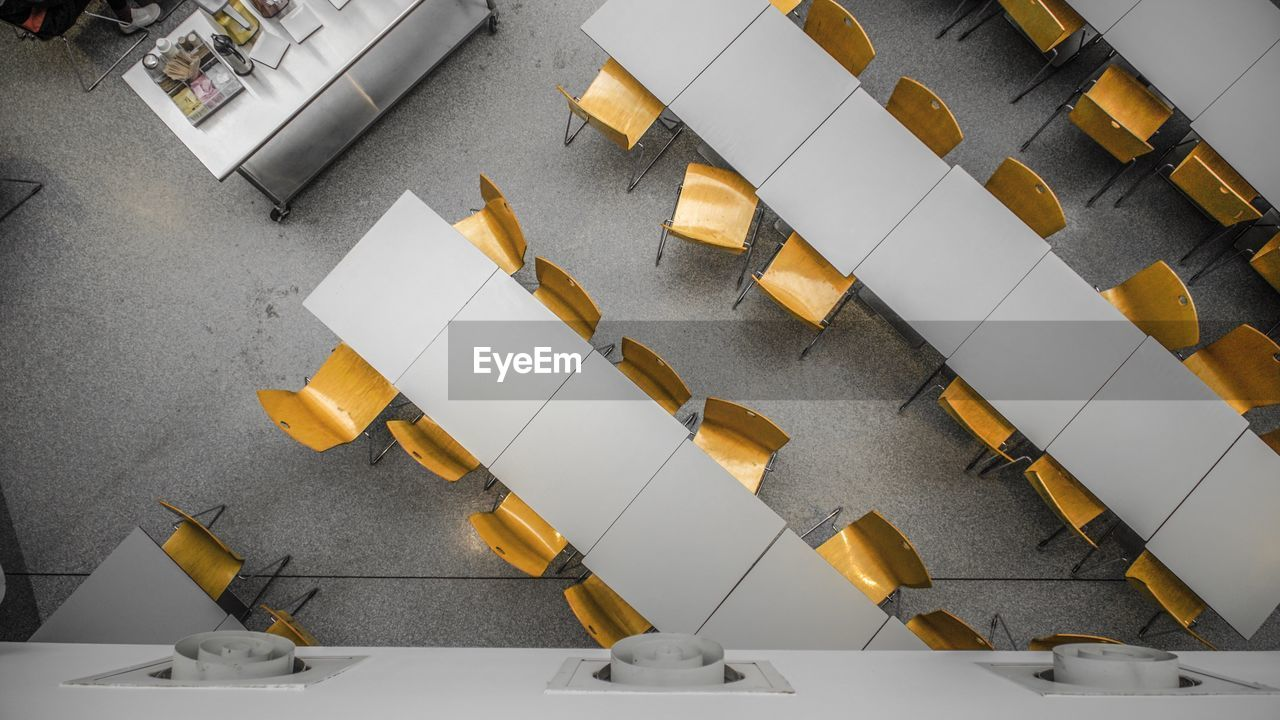 High angle view of chairs by table