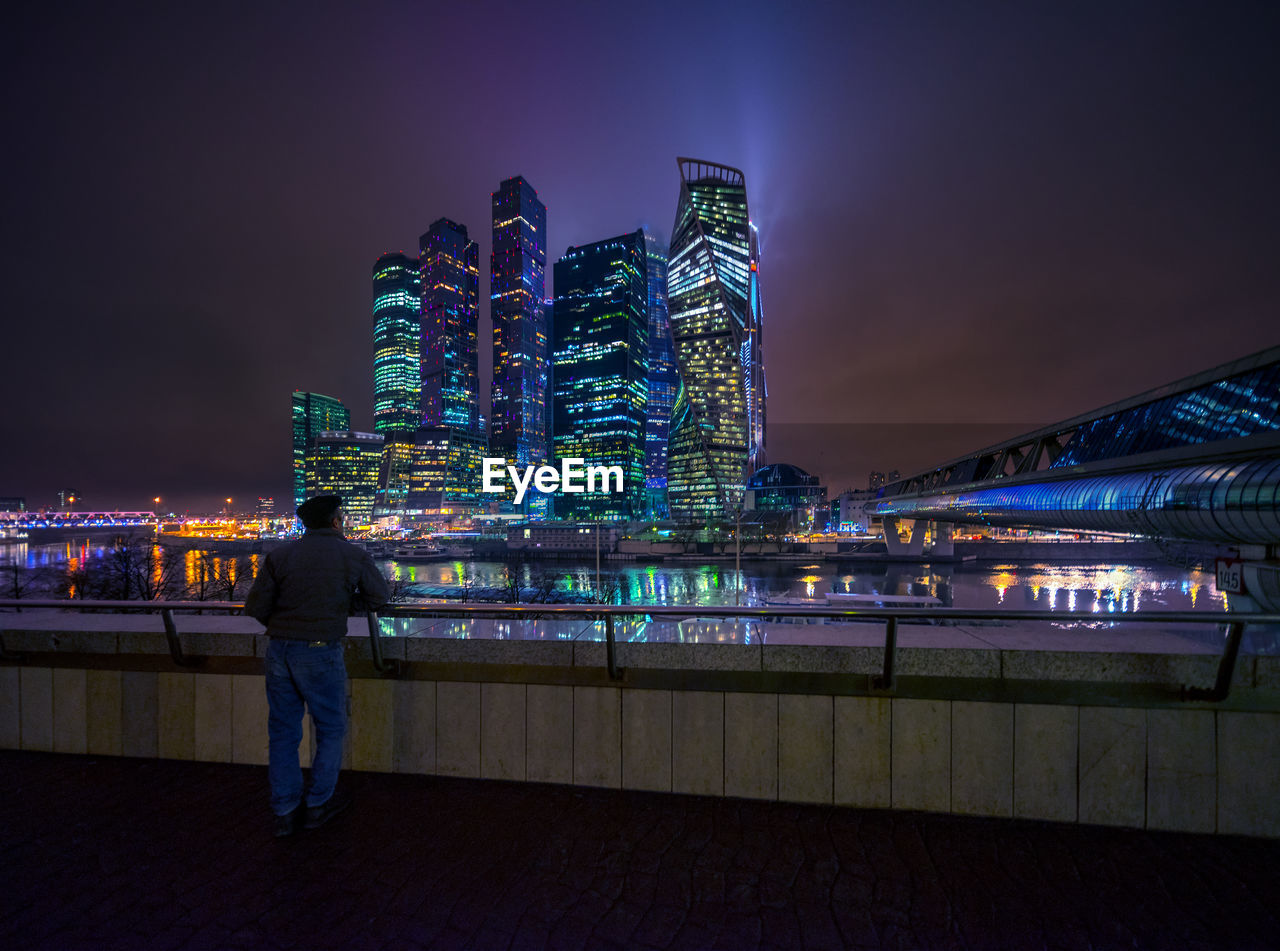 illuminated, architecture, night, building exterior, built structure, city, sky, water, real people, men, building, lifestyles, nature, city life, cityscape, one person, rear view, leisure activity, office building exterior, skyscraper, outdoors, modern, looking at view