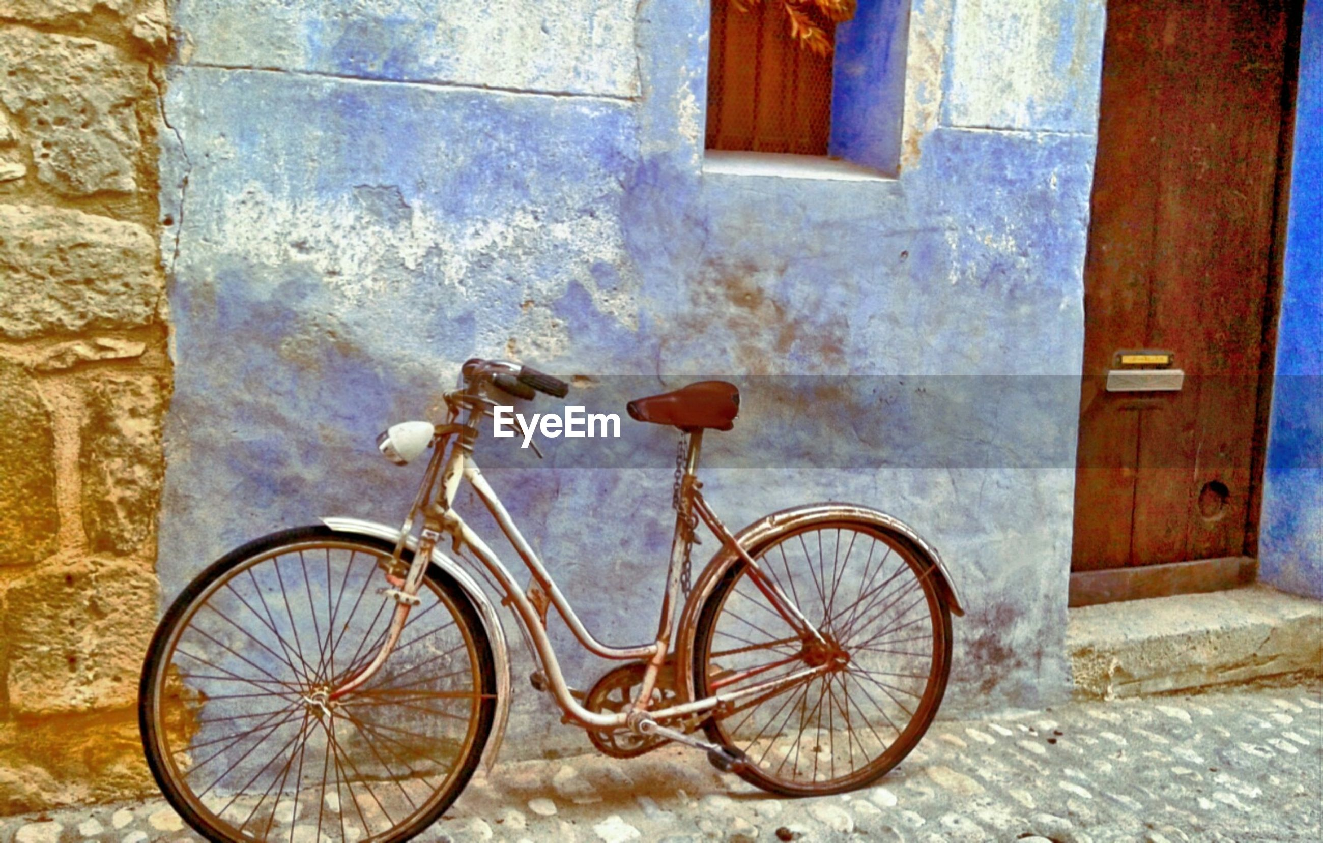 Bicycle parked against old house