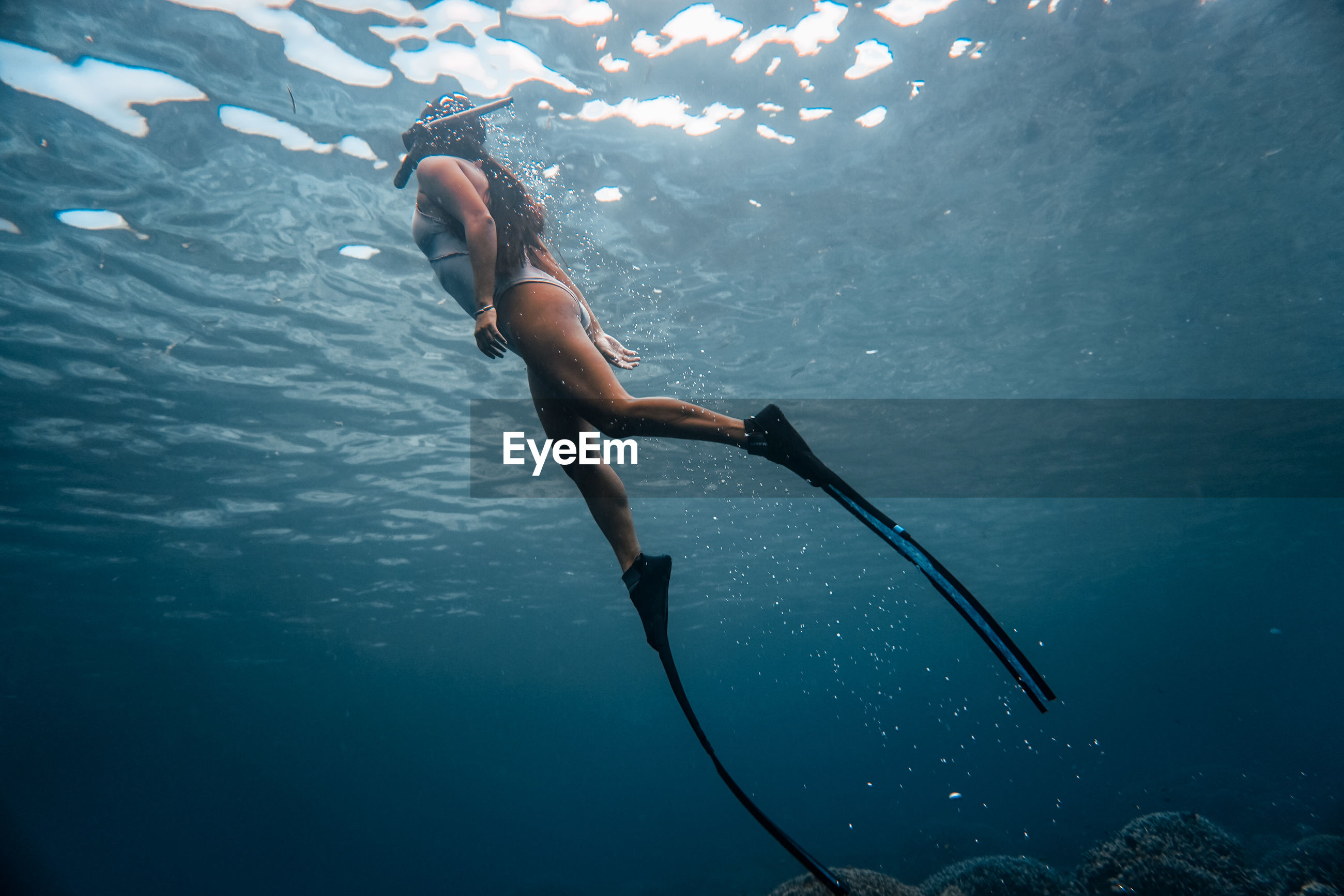 Low angle view of mid adult woman swimming in sea