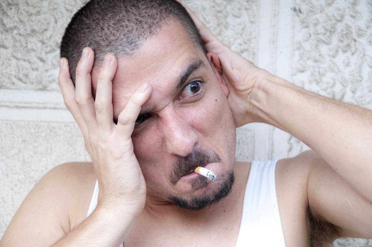 Man smoking cigarette in city
