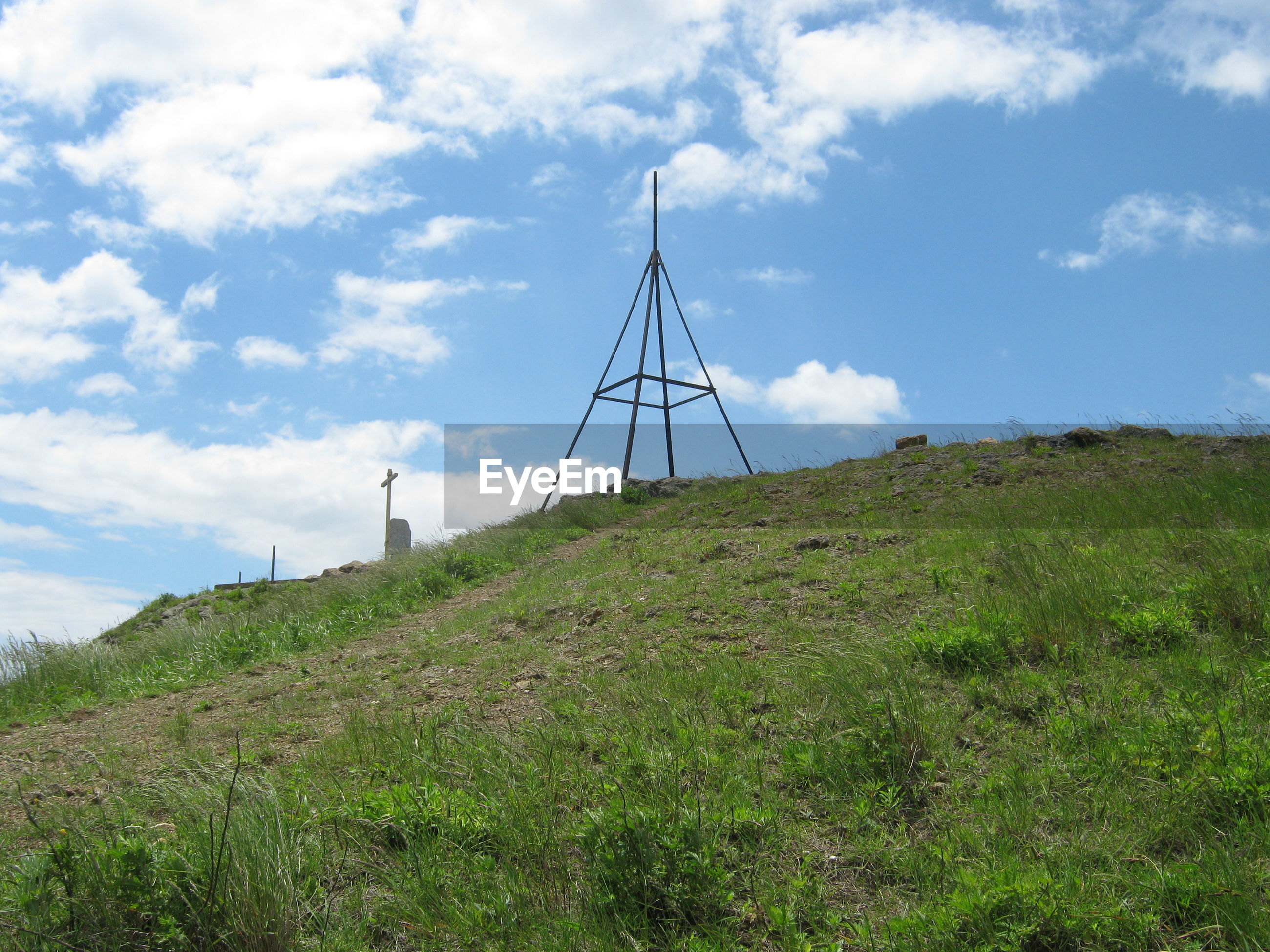 Landmark and cross on the top of mountain against sky