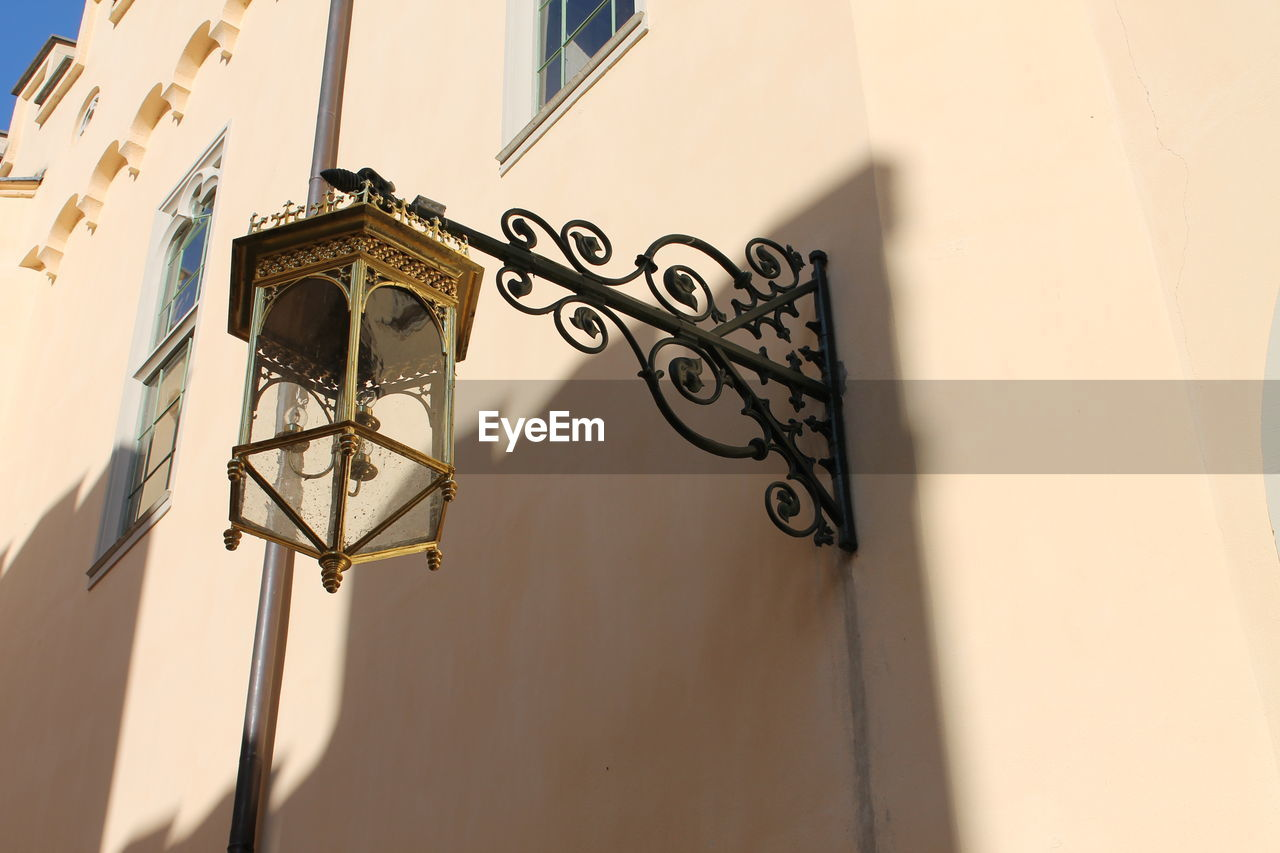 built structure, wall - building feature, architecture, low angle view, building exterior, no people, shadow, lighting equipment, sunlight, day, building, creativity, metal, design, focus on foreground, art and craft, outdoors, close-up, graffiti, electric lamp, ornate