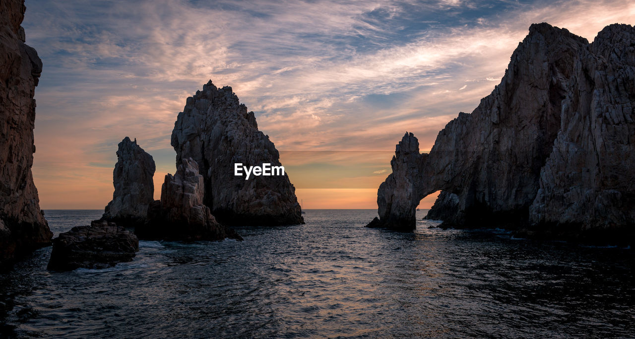 Rock formations in sea against cloudy sky during sunset