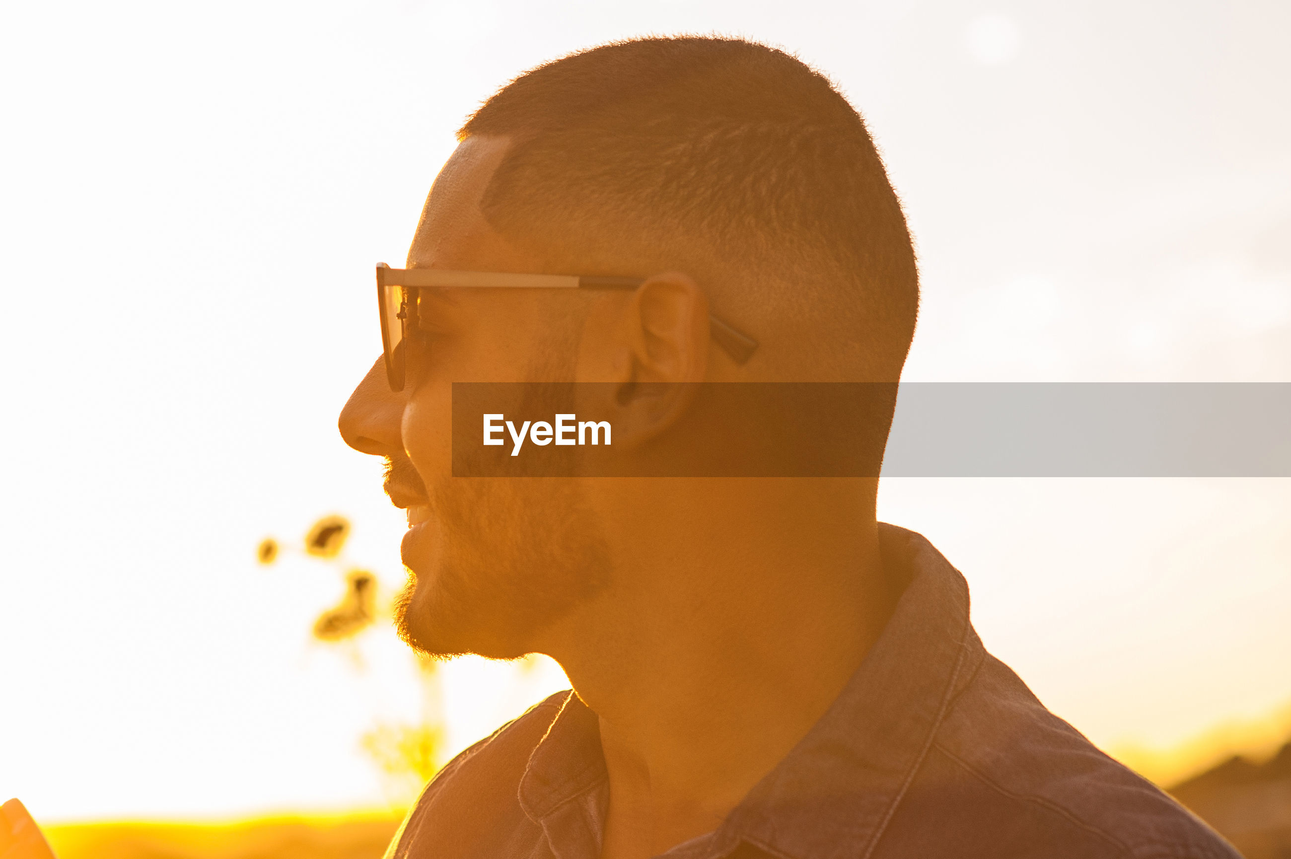 Close-up of man standing by railing during sunset