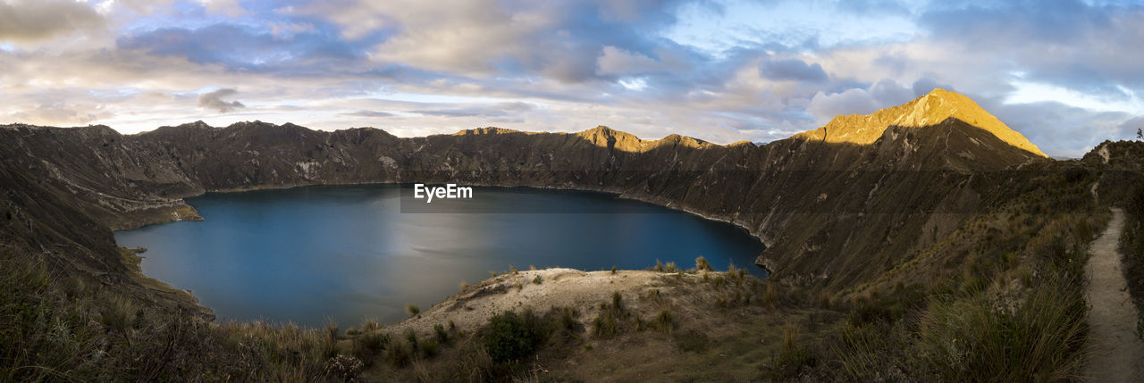 Scenic View Of Crater Lake Surrounded By Mountains Against Sky