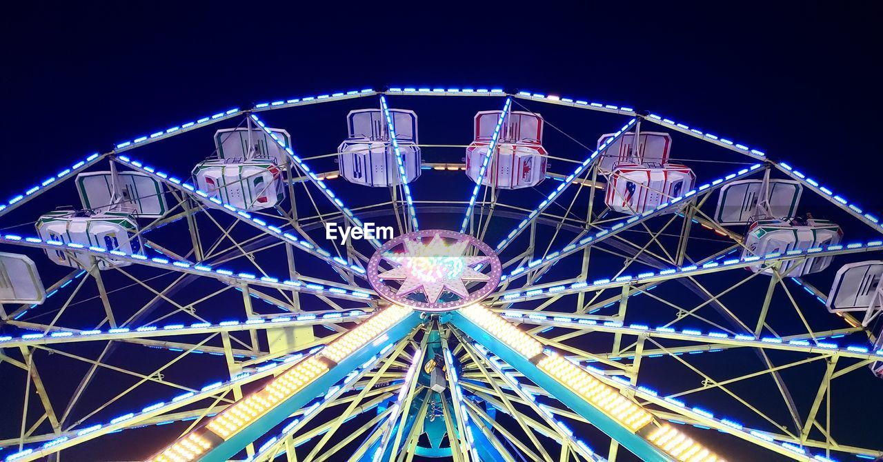 amusement park ride, amusement park, ferris wheel, arts culture and entertainment, sky, illuminated, night, low angle view, no people, architecture, metal, nature, fairground, built structure, leisure activity, clear sky, enjoyment, fun, outdoors, blue, excitement