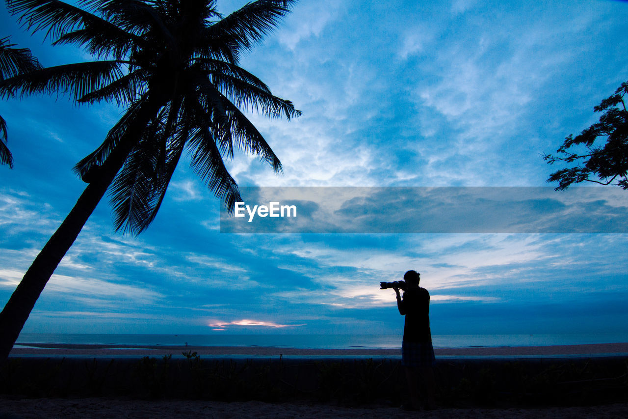 sky, tree, real people, beauty in nature, cloud - sky, tropical climate, palm tree, one person, silhouette, nature, land, scenics - nature, plant, leisure activity, tranquil scene, tranquility, standing, lifestyles, men, photography themes, outdoors, human arm, coconut palm tree