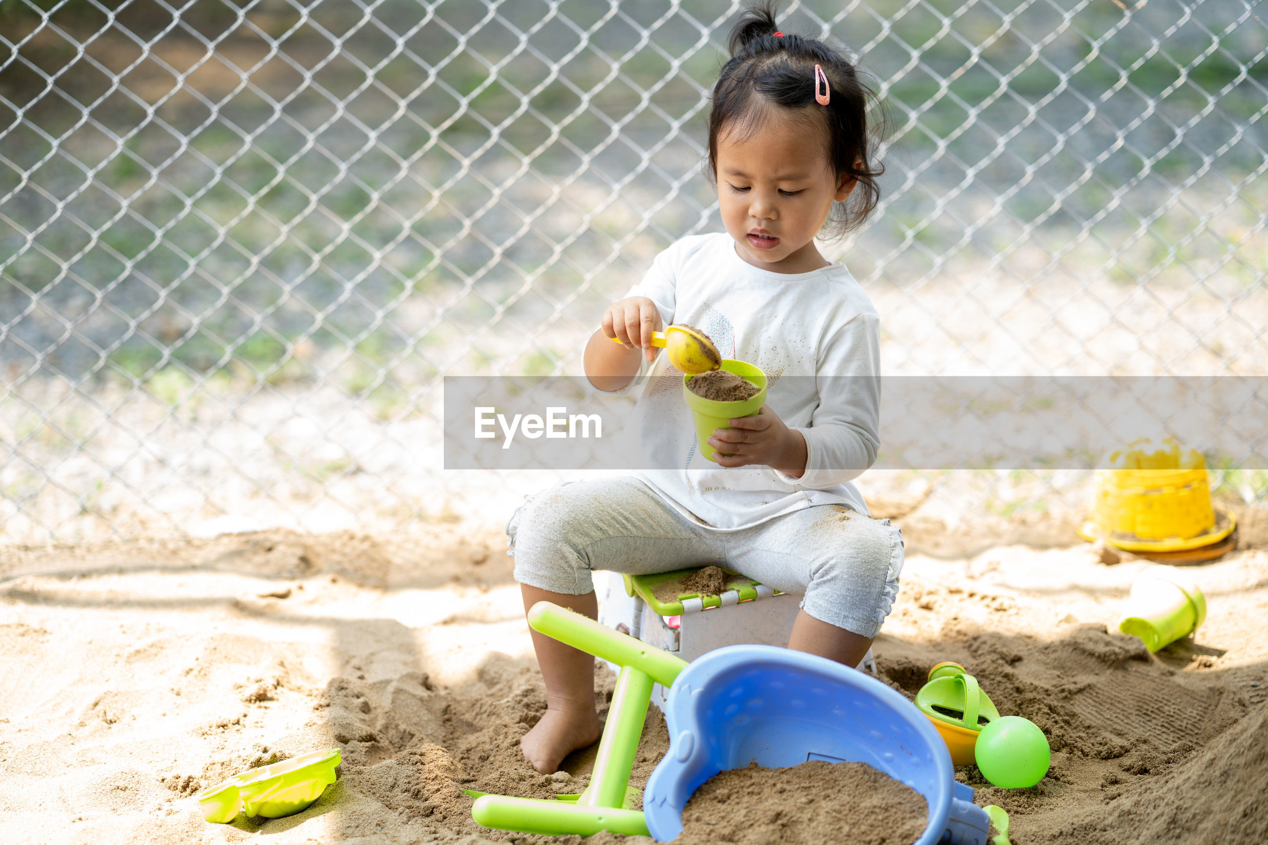 Cute girl playing with toys while sitting outdoors
