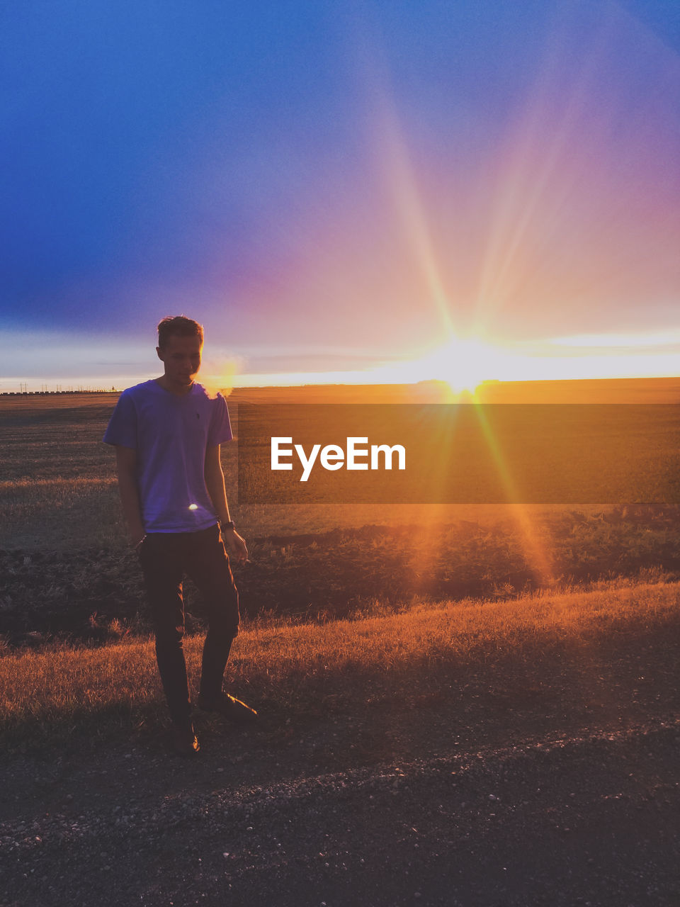 Man walking on road against cloudy sky during sunset